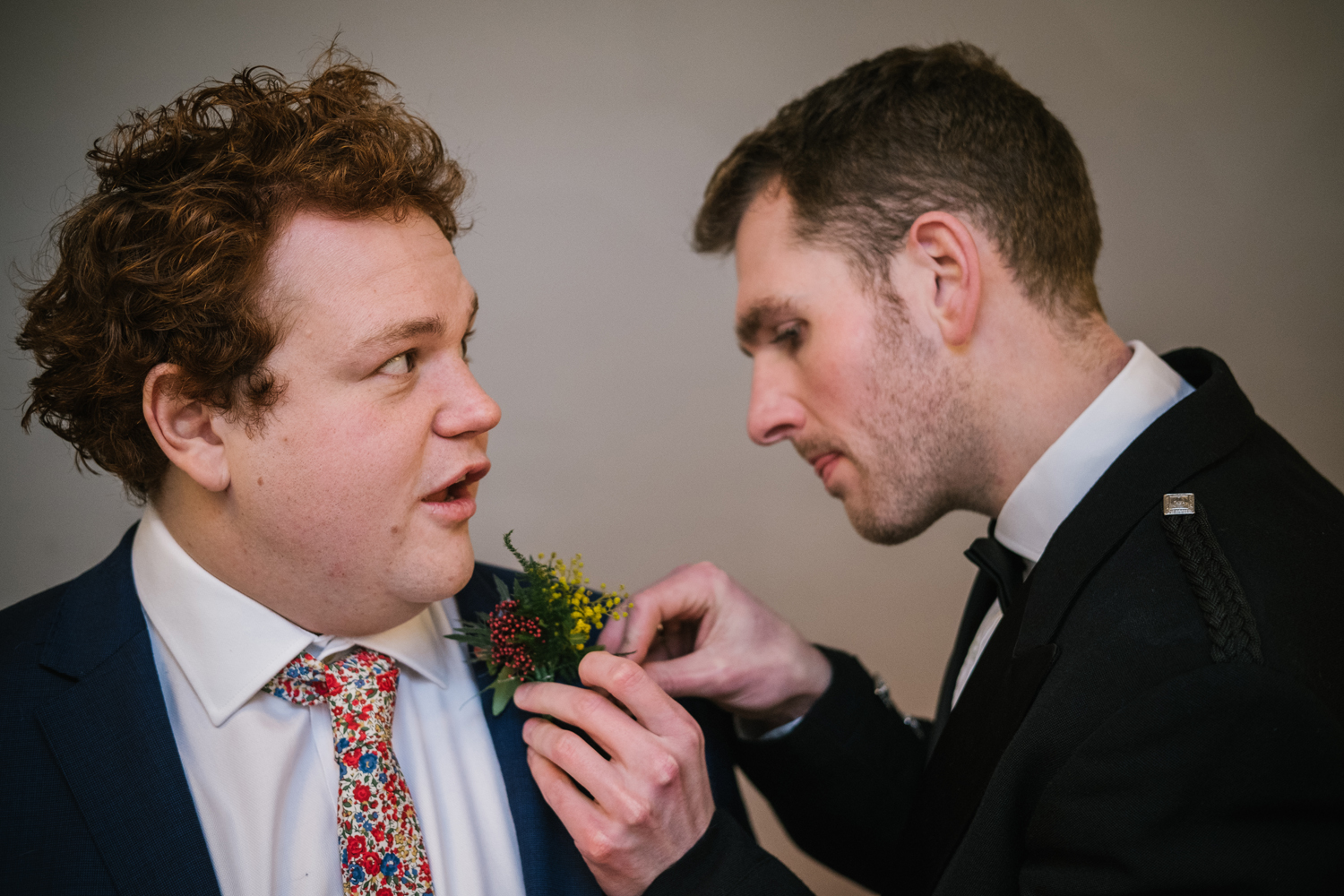 groom getting buttonhole attached by Emma and Rich
