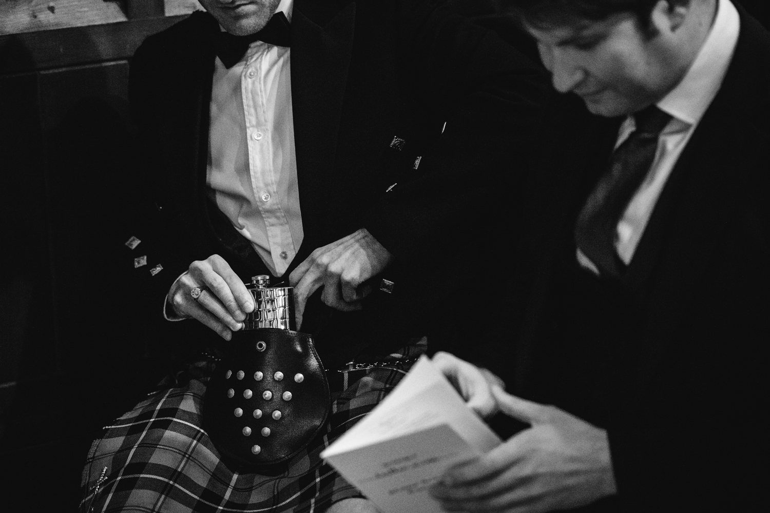 man in cornish tartan kilt hiding hipflask by Emma and Rich