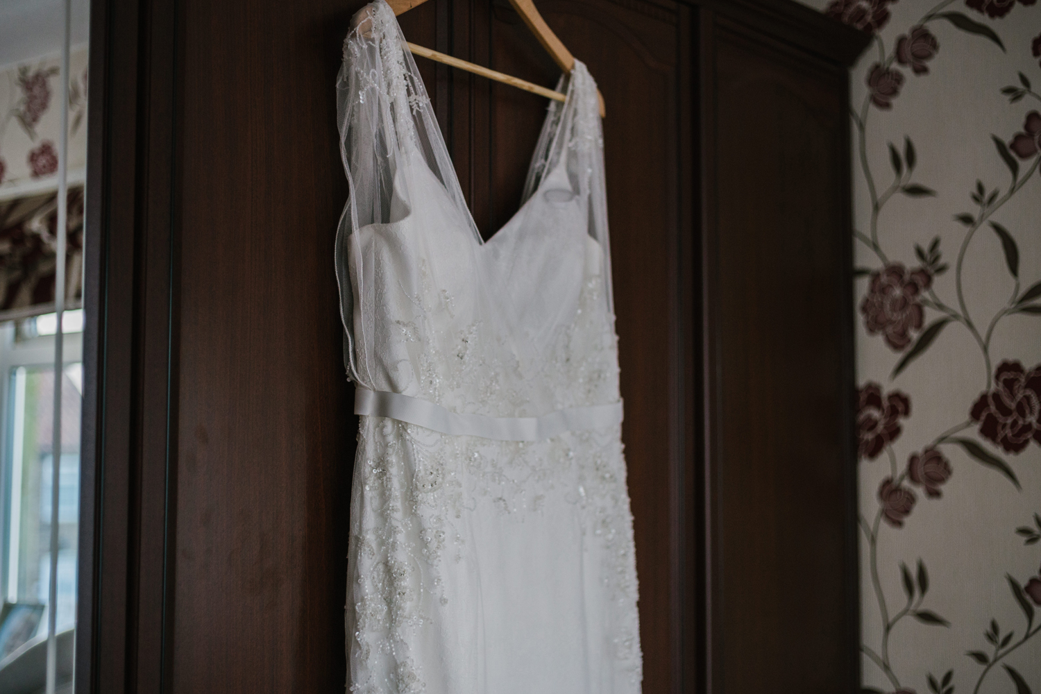 wedding dress hanging on wardrobe by Emma and Rich
