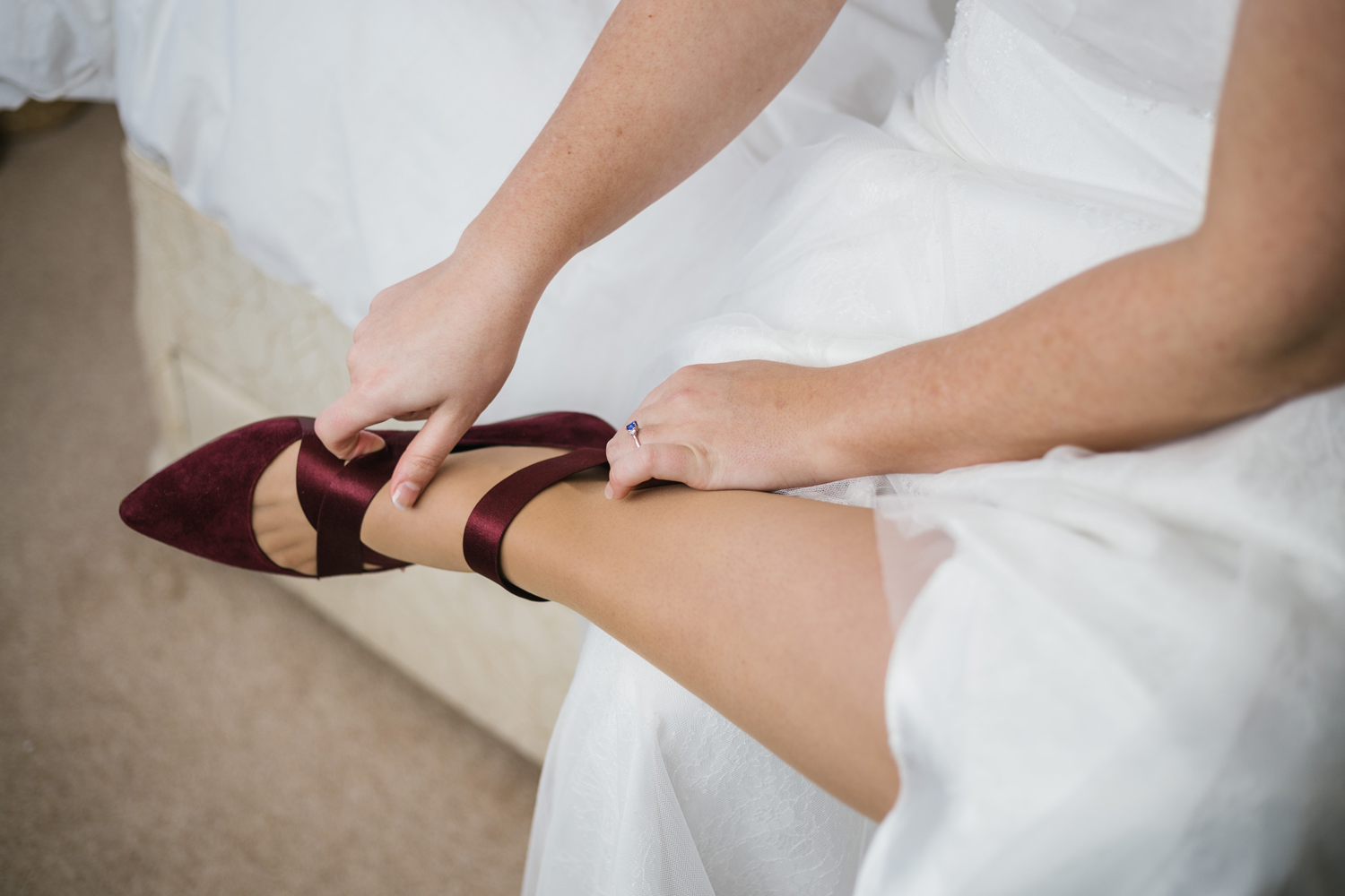 bride putting on maroon wedding shoes by Emma and Rich