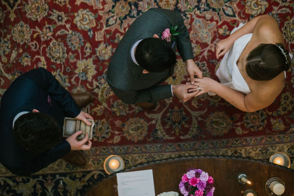 A birds eye view of a groom putting a ring on the brides finger. the best man is stood to the side with the ring box. Middleton Lodge wedding photography by emma and rich.