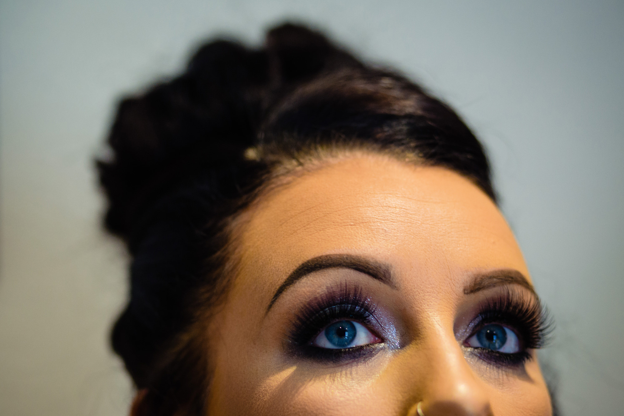 close up of a brides bright blue eyes.