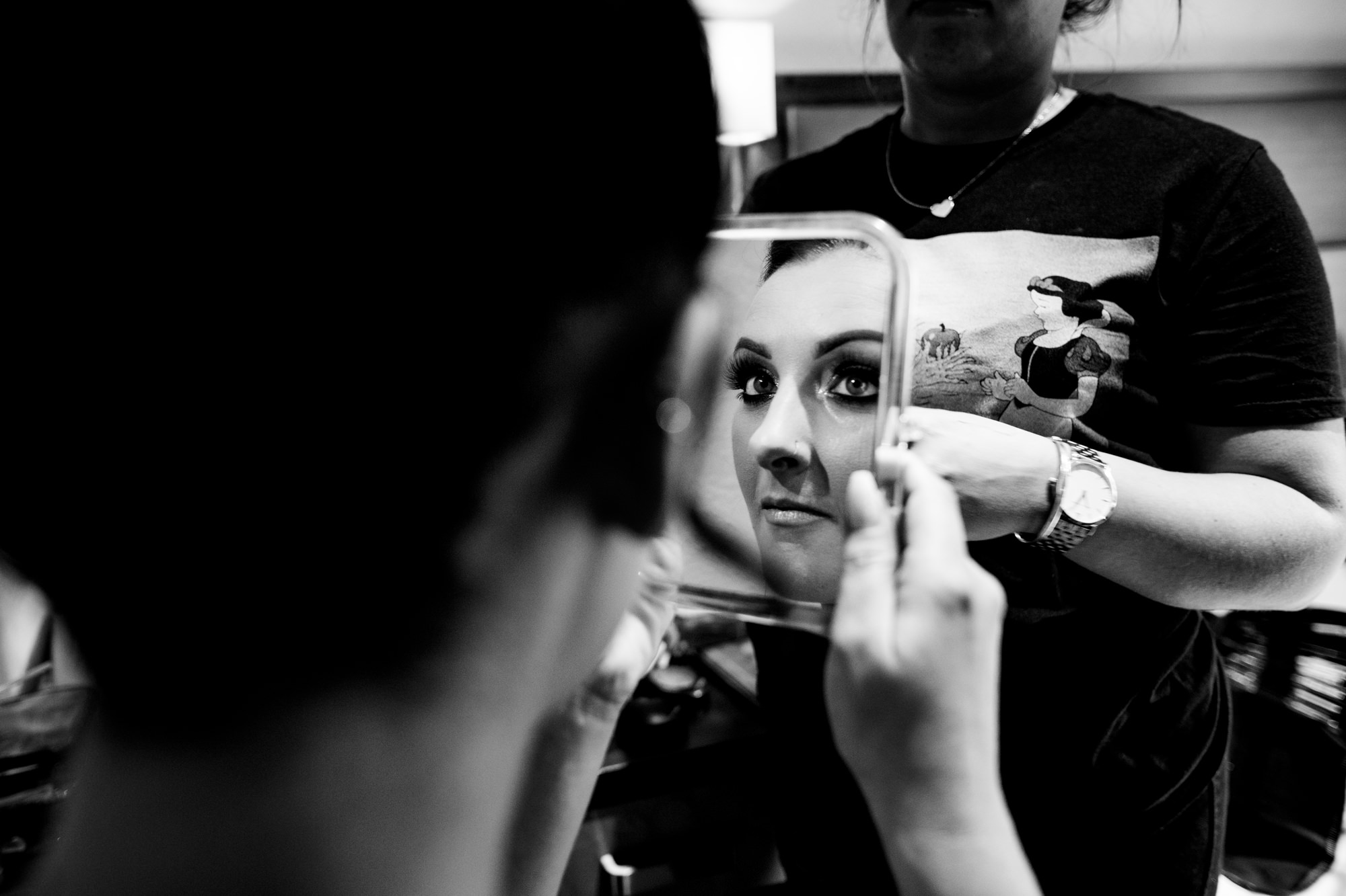 bride checking her make-up in the mirror.