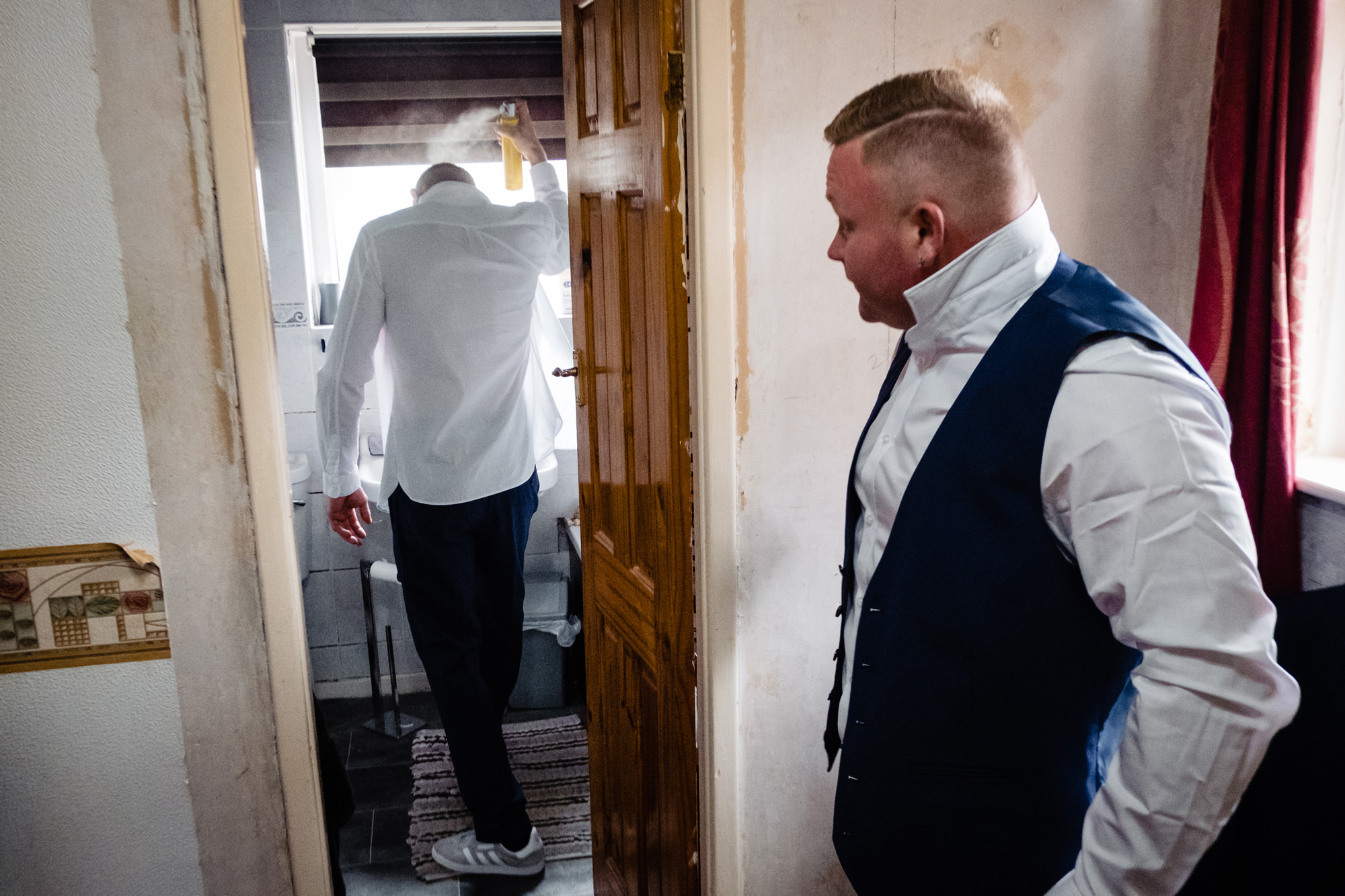 groom using hairspray in the bathroom as an usher looks on.