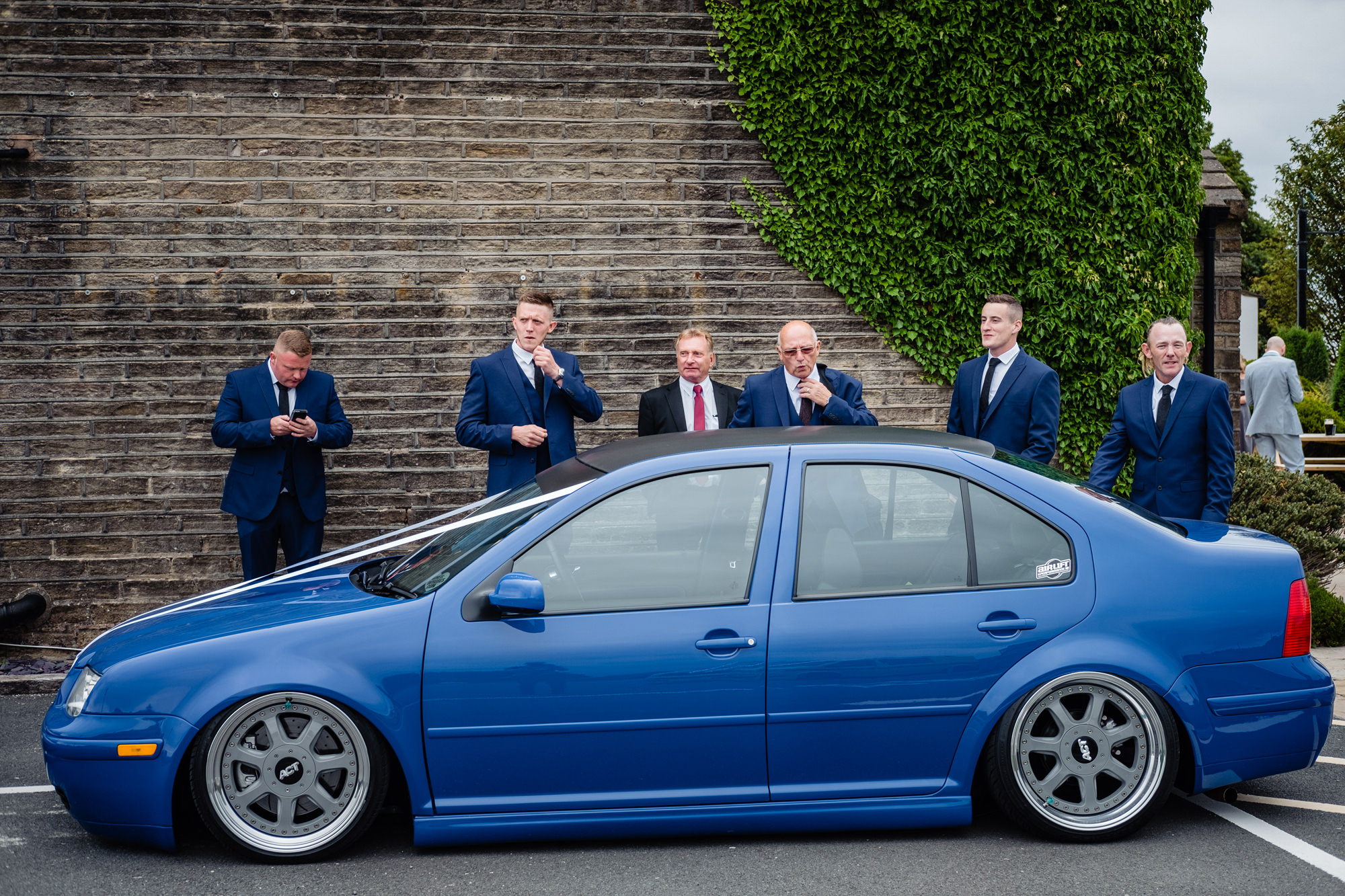 groom and groomsmen in blue suits standing behind a blue v w show car. huntsman inn wedding photography by emma and rich.