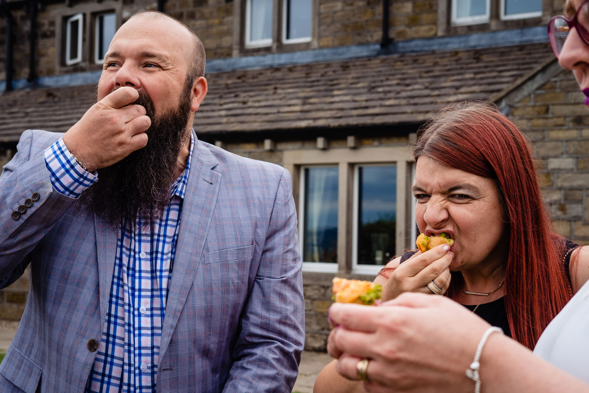two wedding guests chomping on canapes.