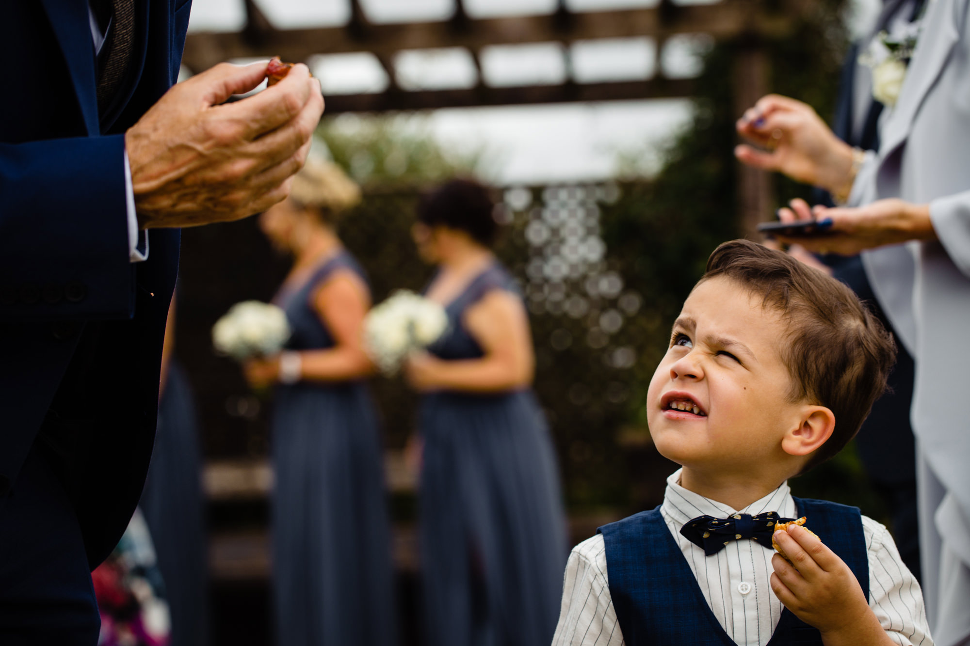 page boy looking uncertain whilst eating a canape. huntsman inn wedding photography by emma and rich.