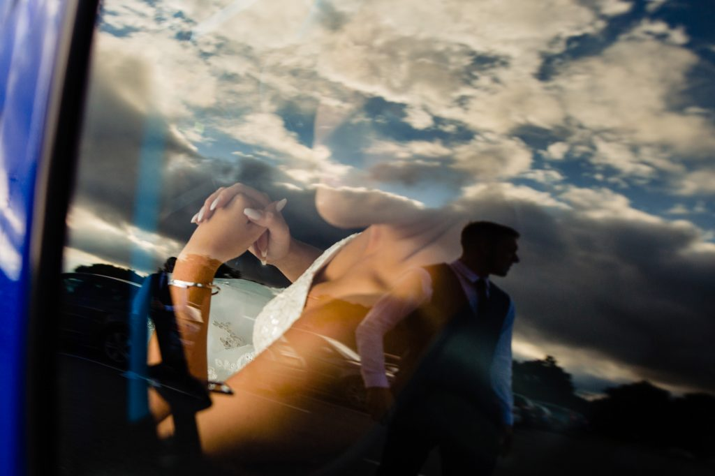 bride looks out of car window. her groom is in the reflection. huntsman inn wedding photography by emma and rich.