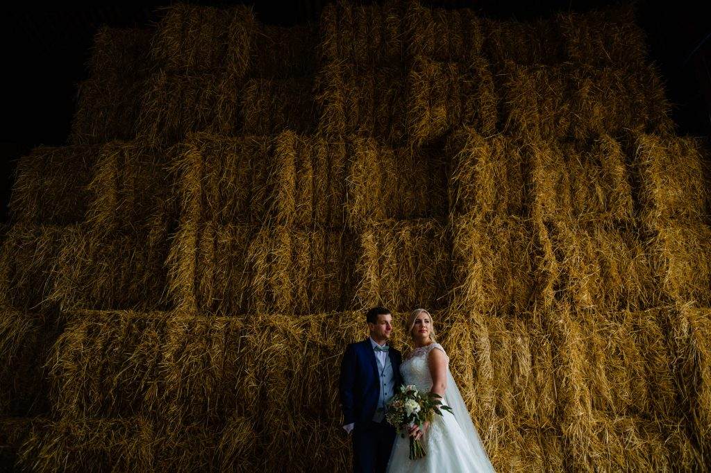 bride and groom pose for a picture in front of a huge haystack. west sussex wedding photography by emma and rich.