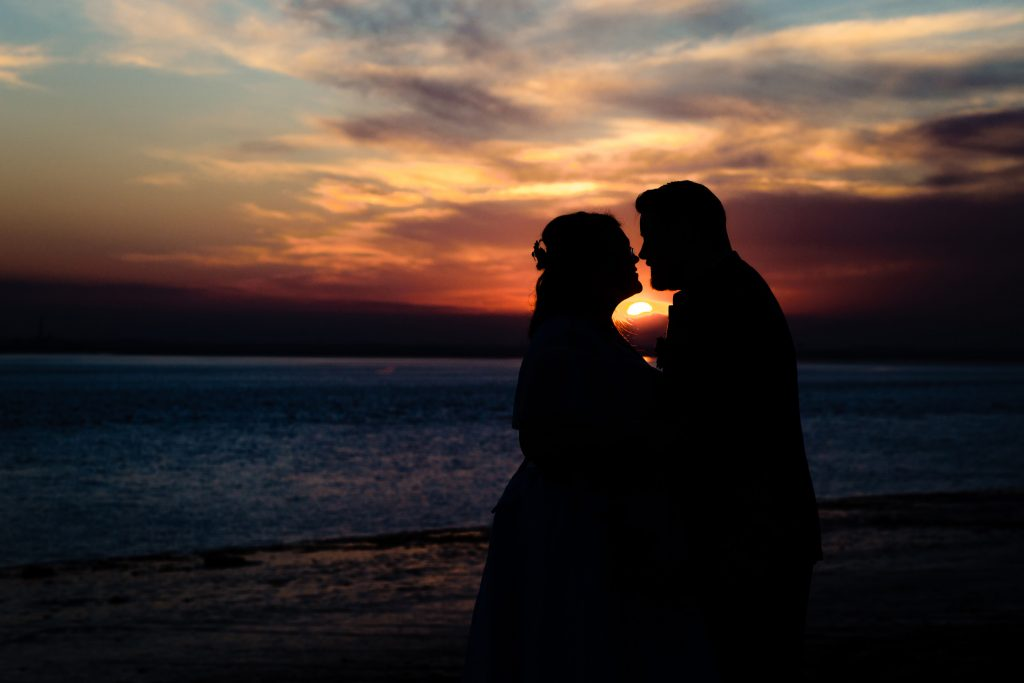 a silhouette of a bride and groom about to kiss outside the country park inn in the sunset, they're stood on the banks of the river humber. wedding photography by emma and rich.