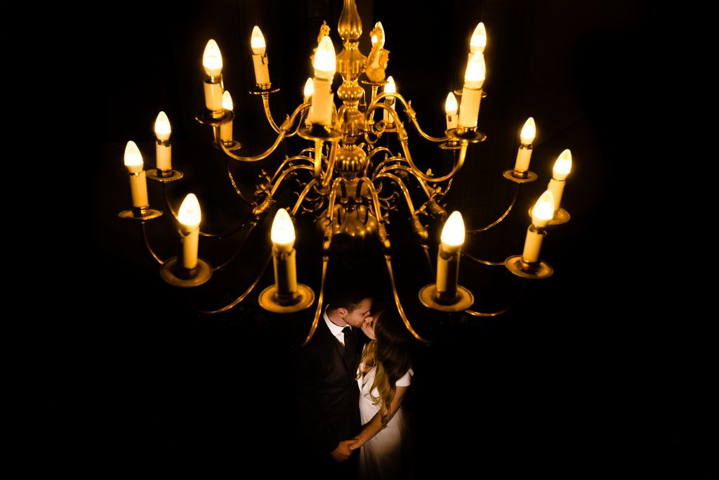 a bride and groom kiss beneath a chandelier. whitley hall wedding photography by emma and rich.