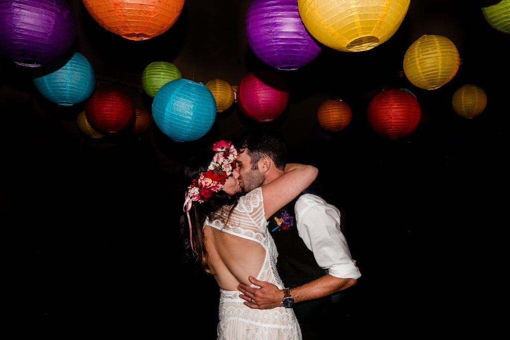 bride and groom kissing under rainbow lanterns