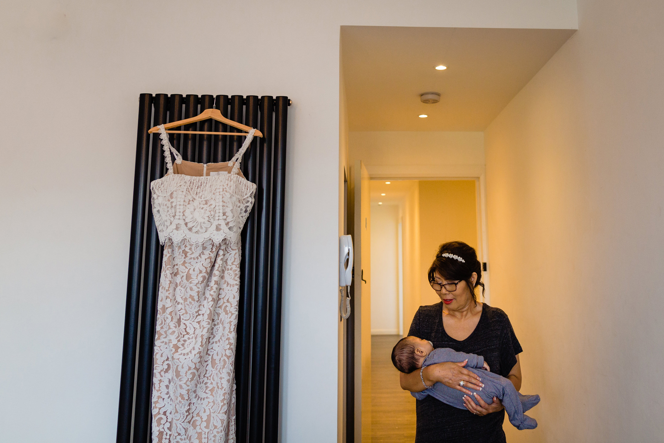 a wedding dress hangs on a tall radiator as a lady cradles a baby in the hallway. asylum wedding photography by emma and rich.