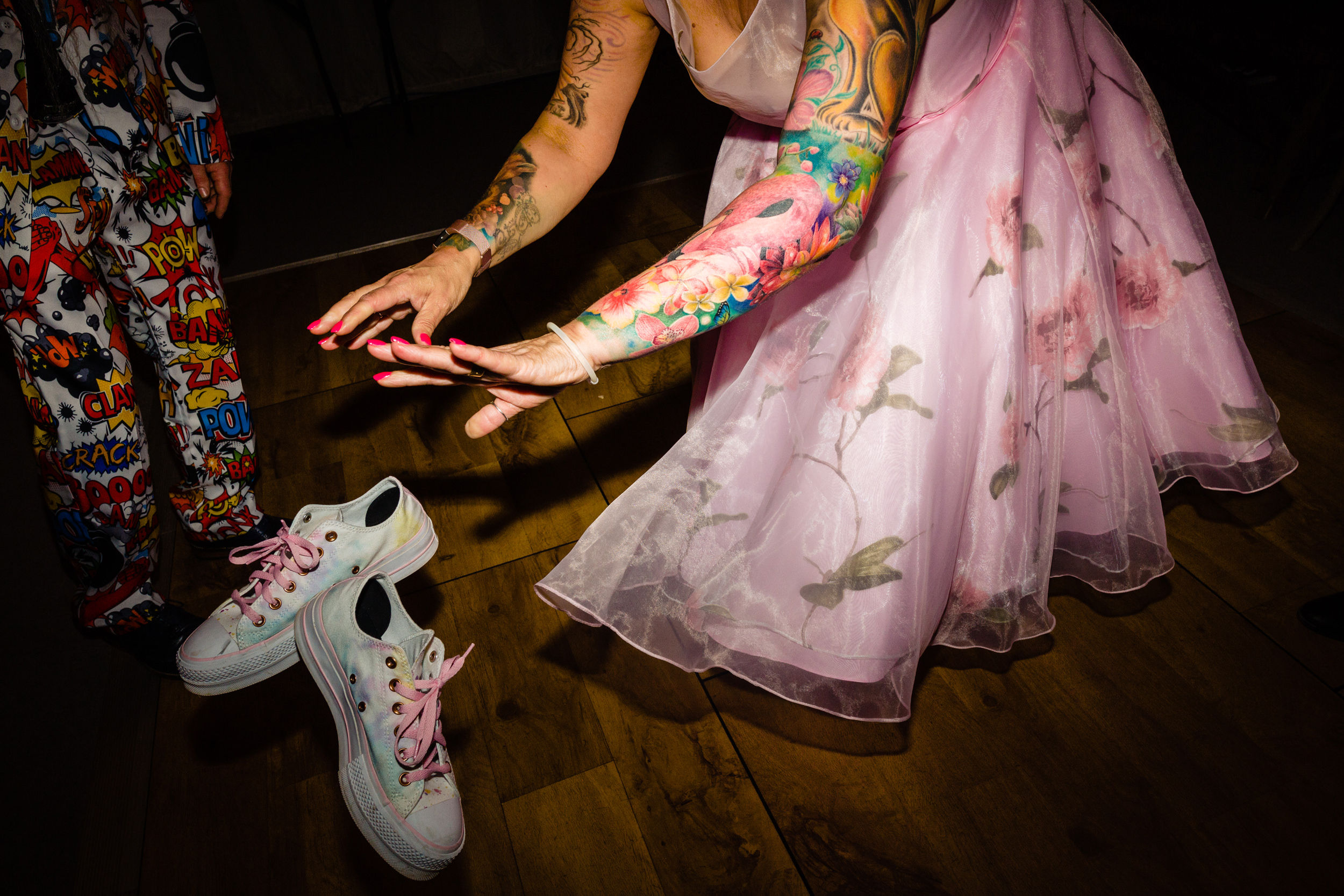 bride removes her shoes on the dancefloor. wold top brewery wedding photography by emma and rich.
