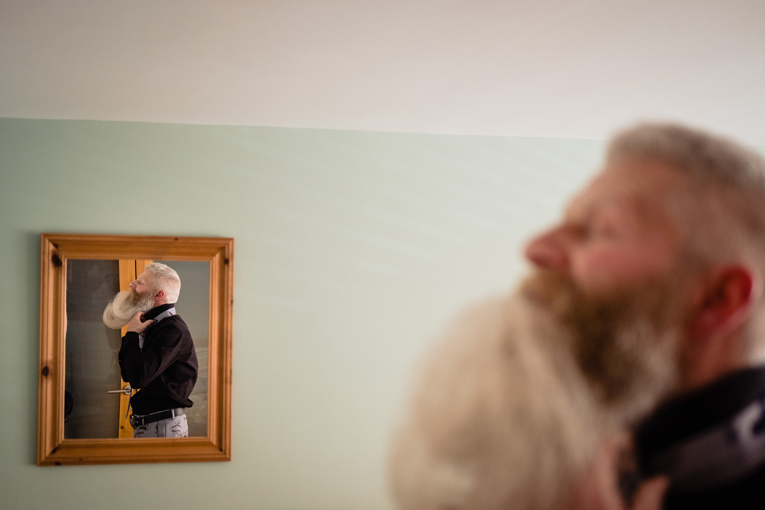 a groom holds his long beard in his mouth as he puts on his tie. wold top brewery wedding photography by emma and rich.