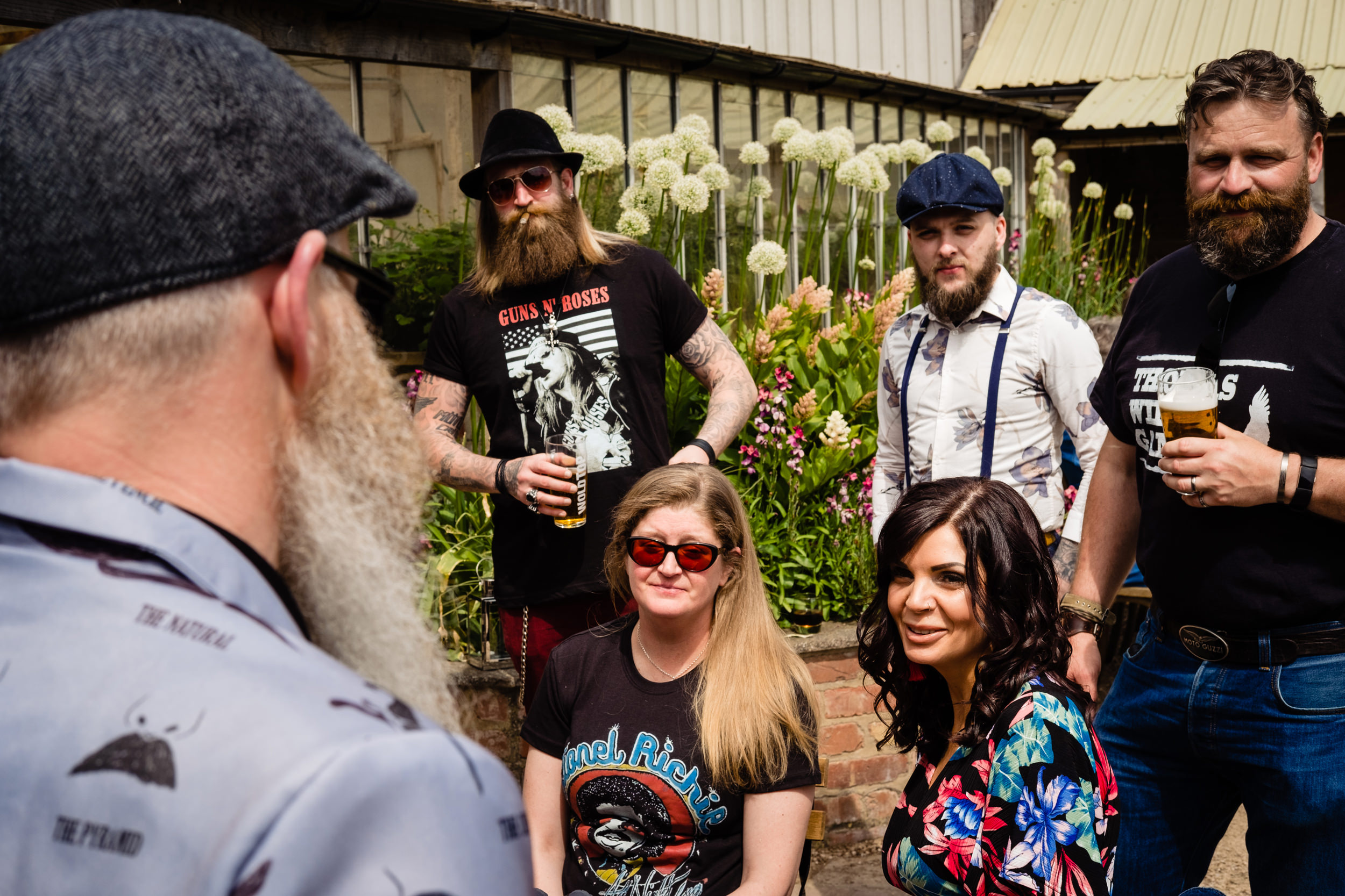 a group of wedding guests with beards and band t-shirts talk to the groom.