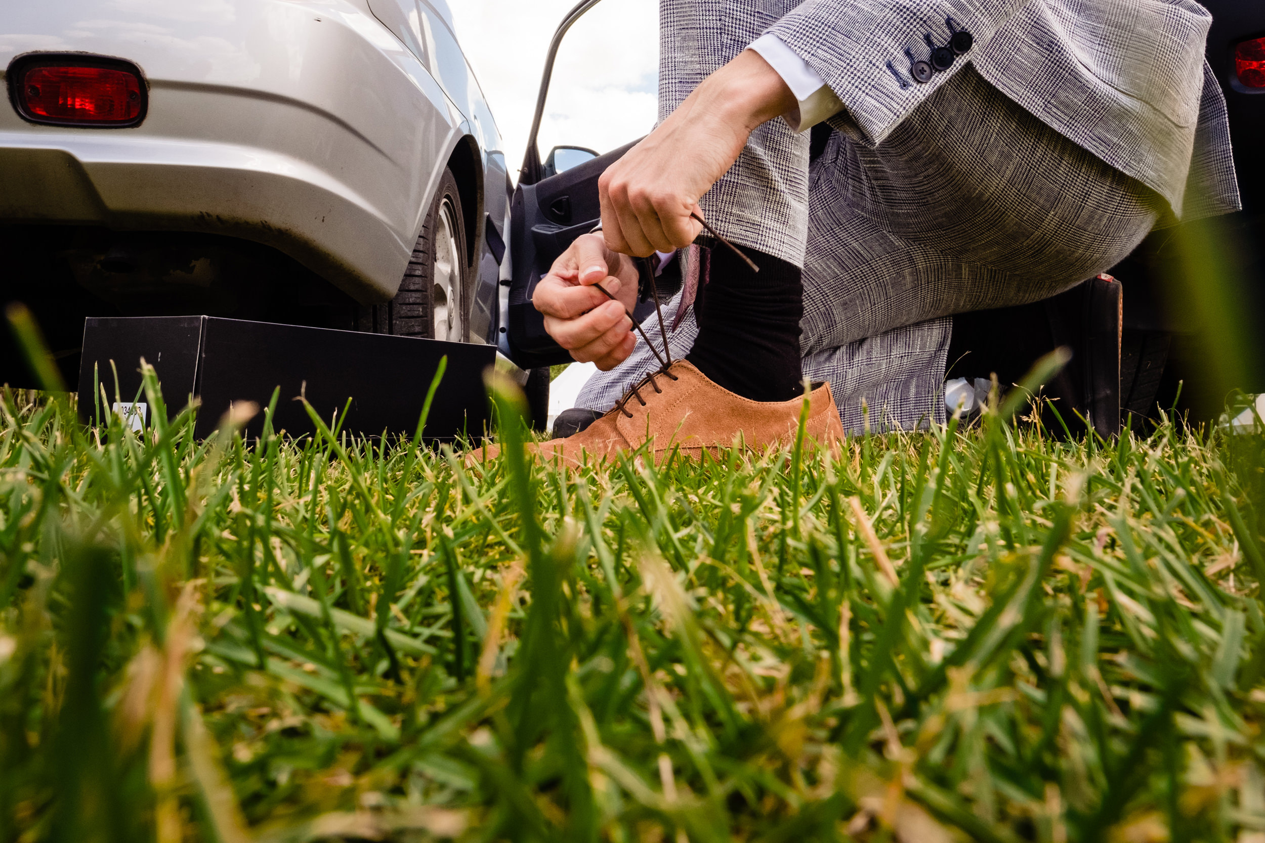 groom lacing up shoes in car park. maybush wedding co wedding photography by emma and rich.