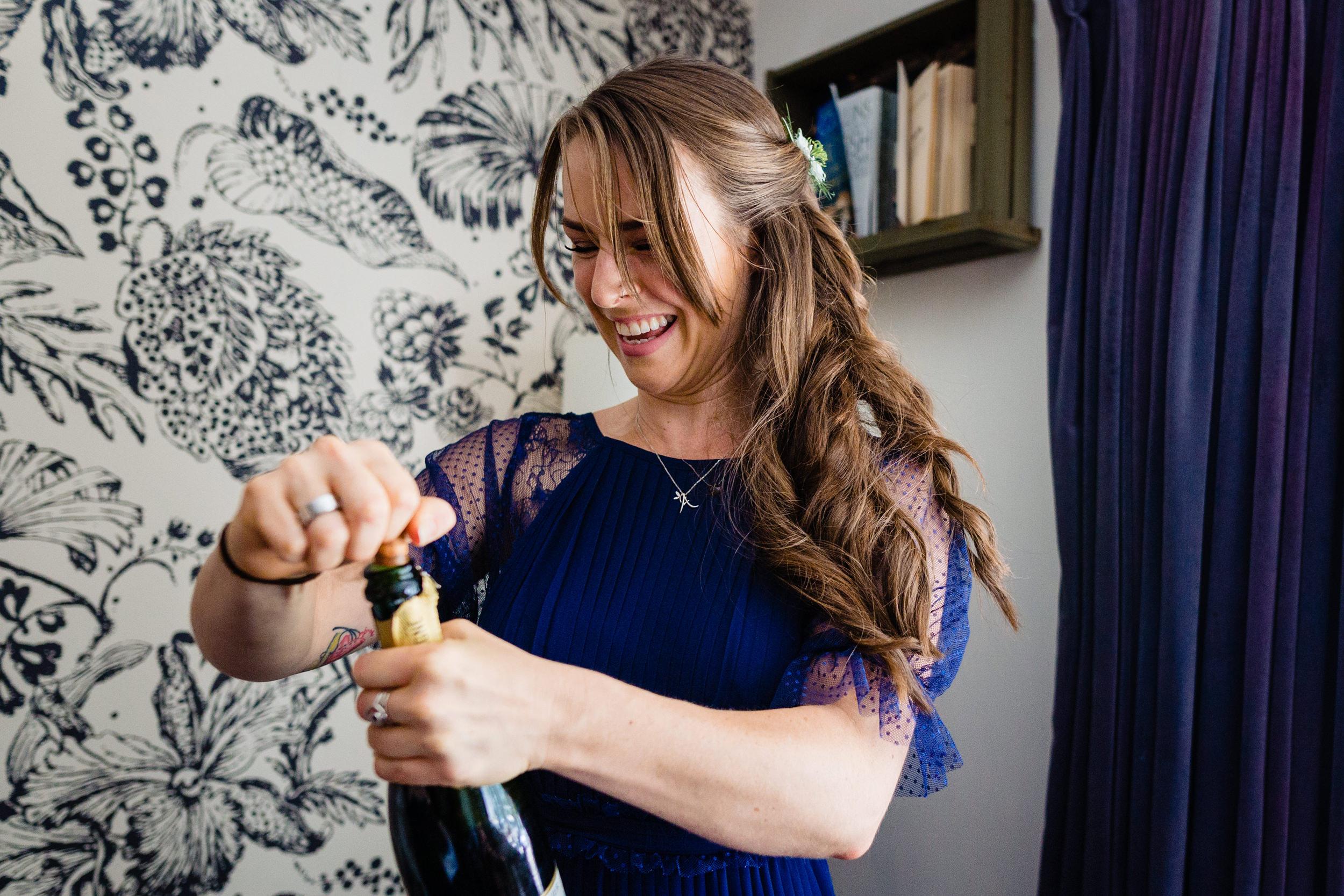 bridesmaid uncorking champagne. maybush wedding co wedding photography by emma and rich.
