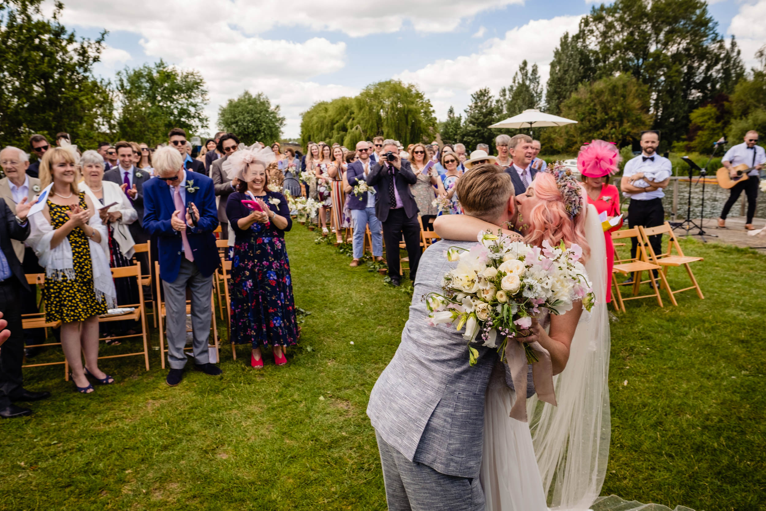 first kiss at wedding as guests applaud. maybush wedding co wedding photography by emma and rich.