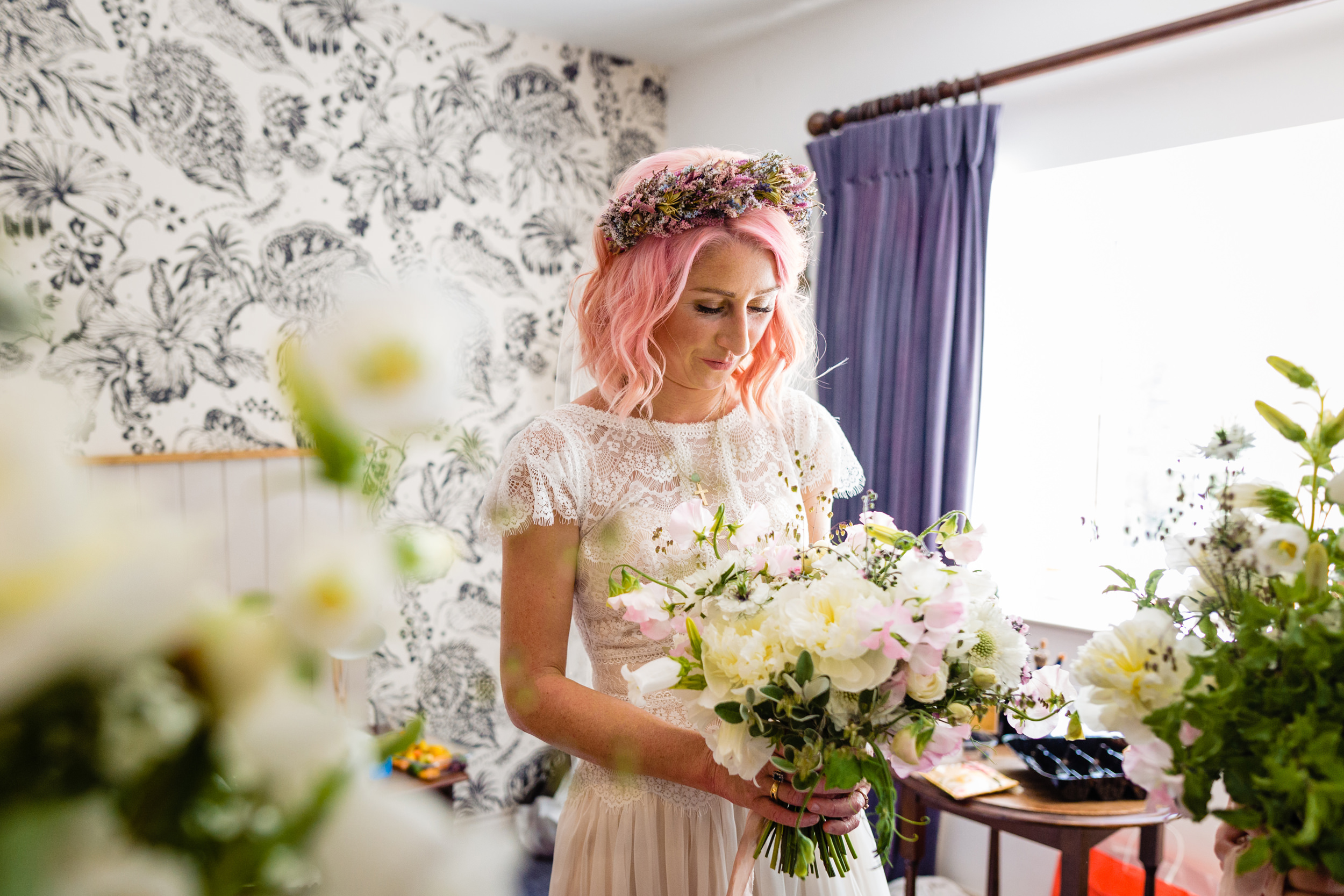 bride admiring her bouquet. maybush wedding co wedding photography by emma and rich.
