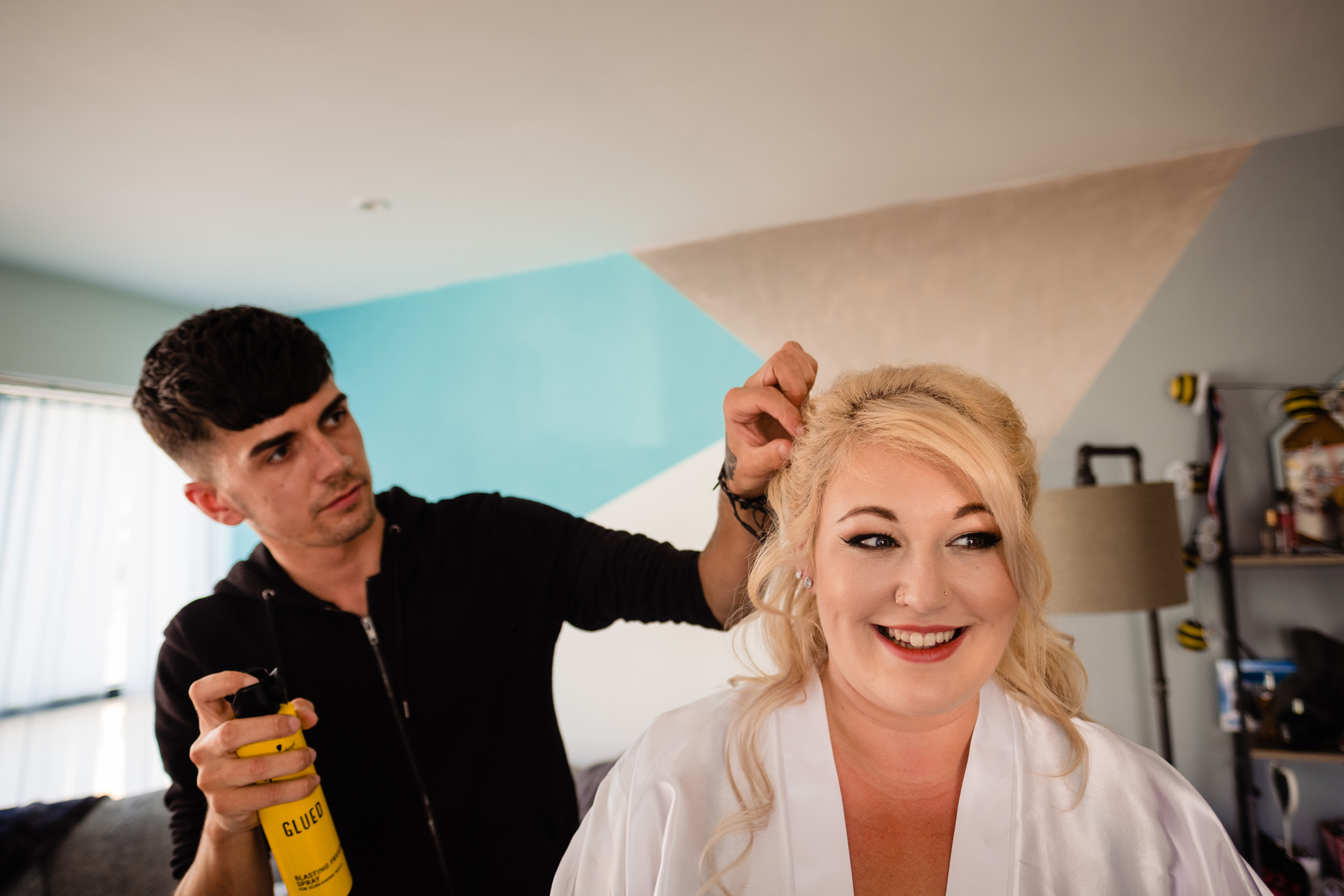 bride getting hair fixed with hairspray. plough inn, hathersage wedding photography by emma and rich.