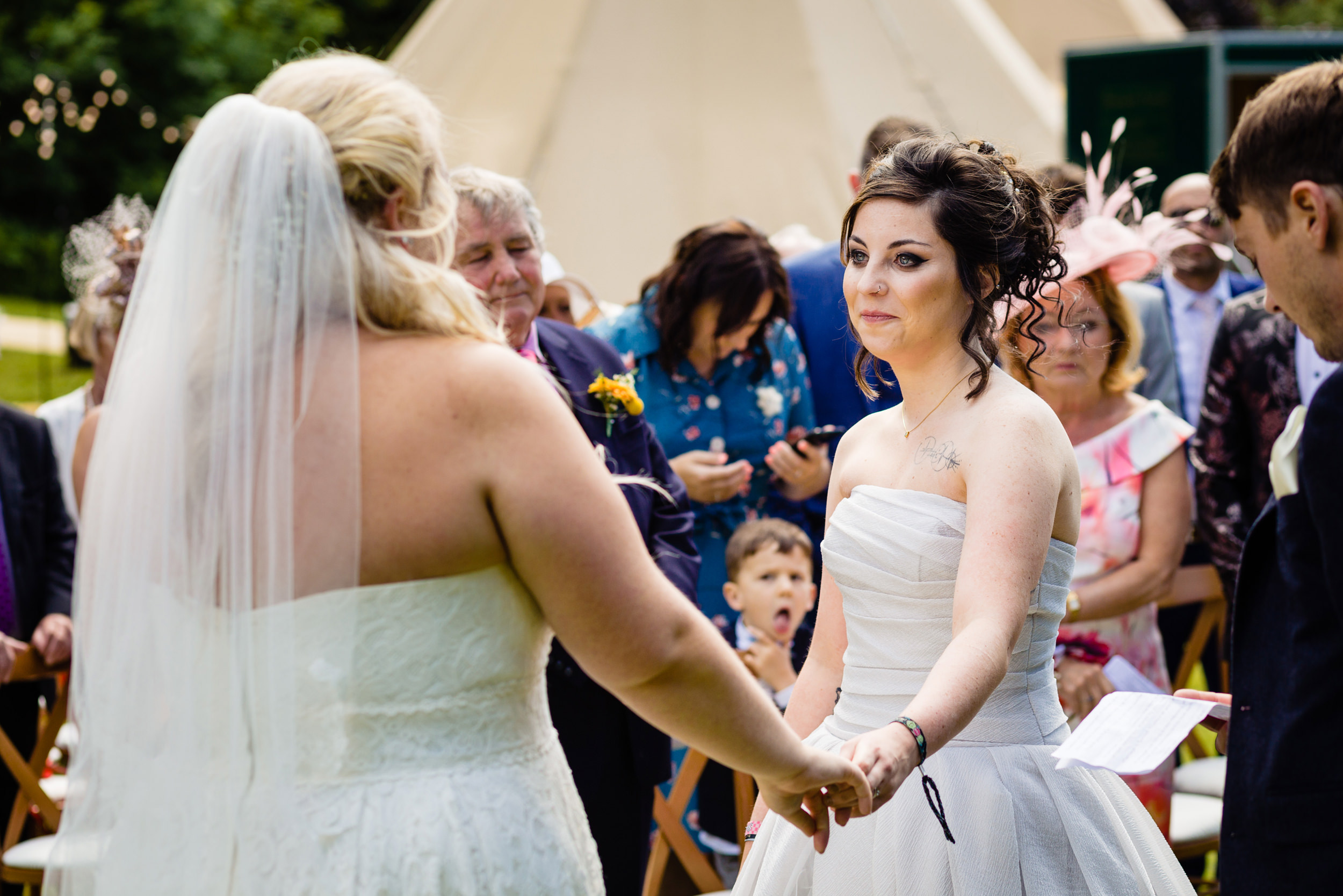 bride looking lovingly at her soon to be wife in the ceremony. plough inn, hathersage wedding photography by emma and rich.