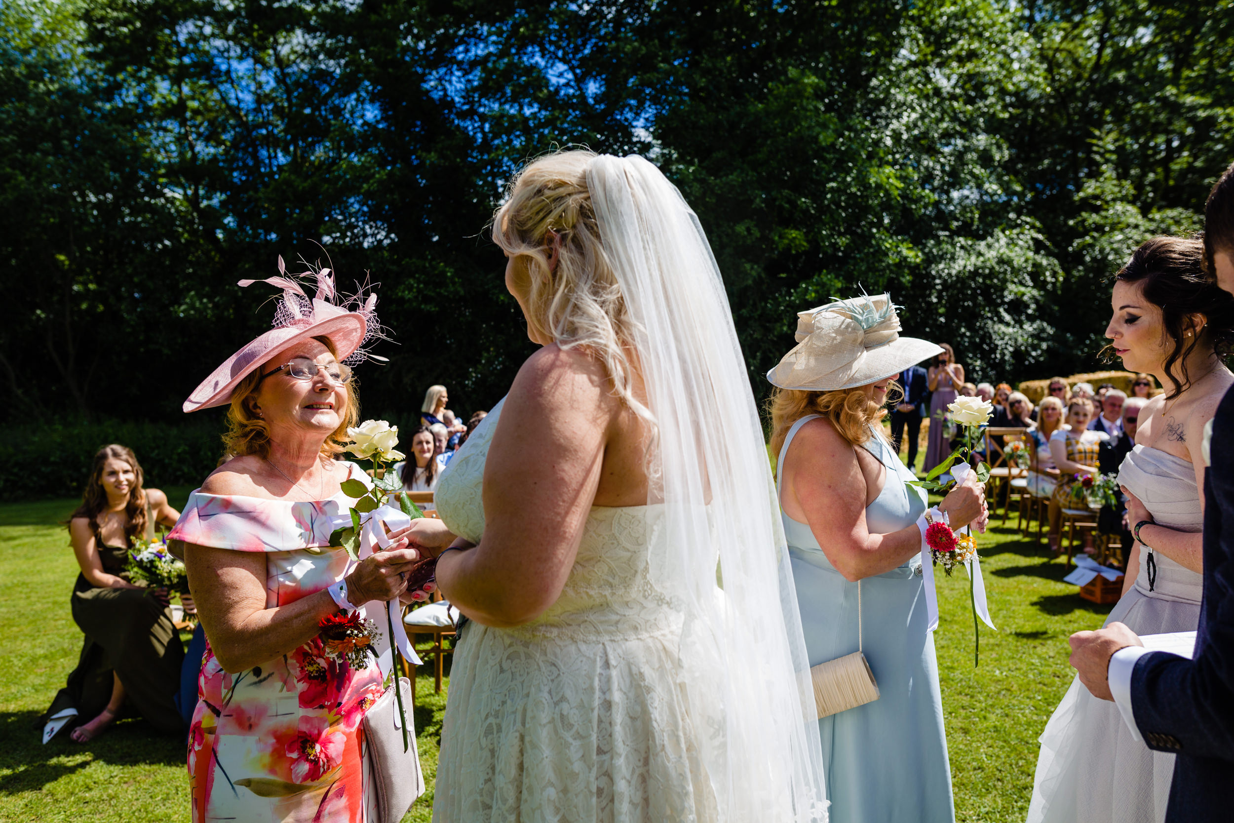 brides give roses to their mothers during wedding ceremony. plough inn, hathersage wedding photography by emma and rich.