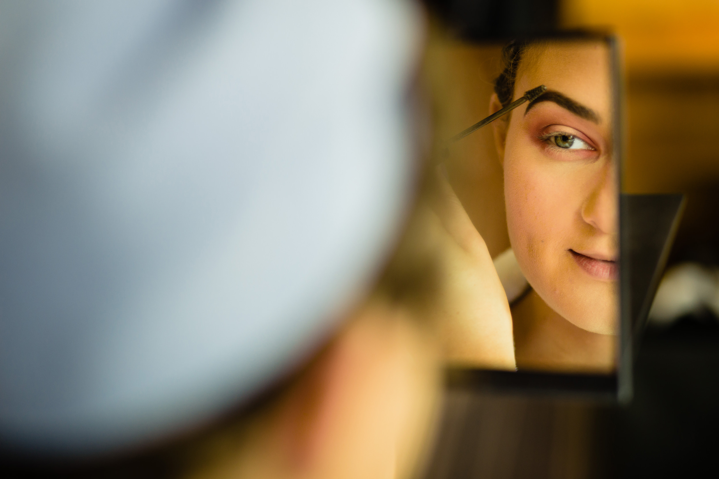 close-up of lady doing eye makeup. plough inn, hathersage wedding photography by emma and rich.