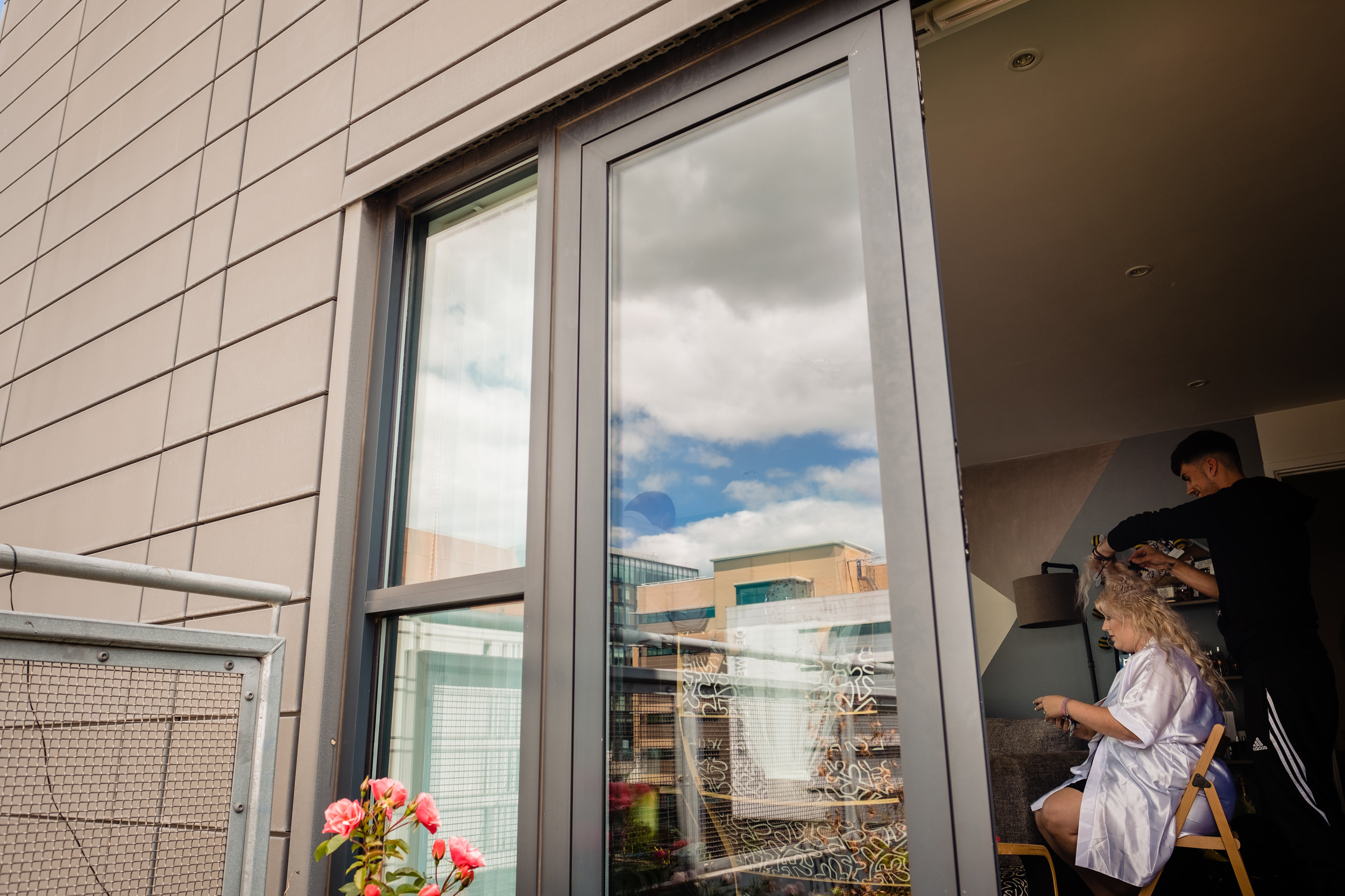 bride having her hair done. city reflected in window. plough inn, hathersage wedding photography by emma and rich.