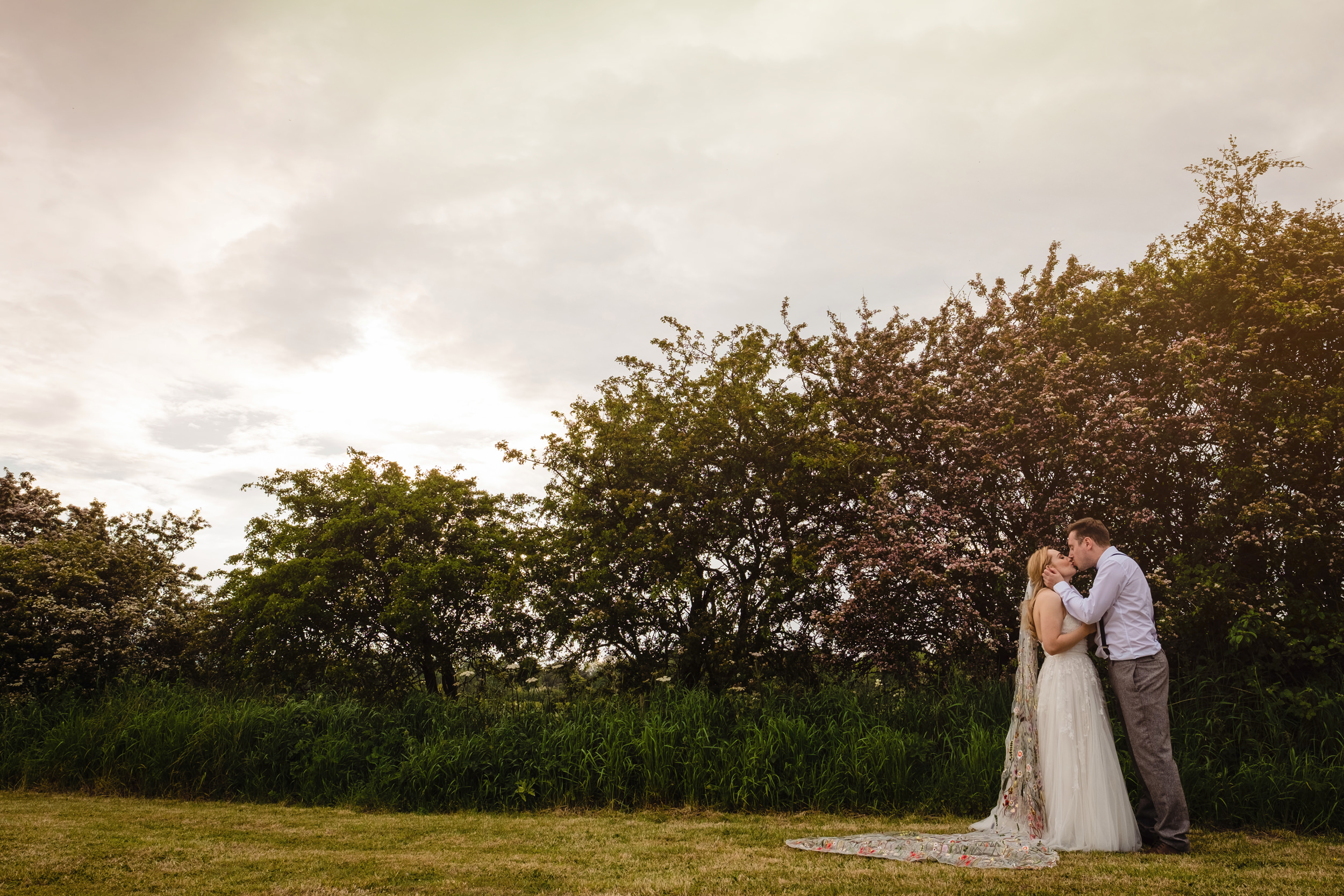 newlyweds in a field kissing. wildwood and eden wedding photography by emma and rich.
