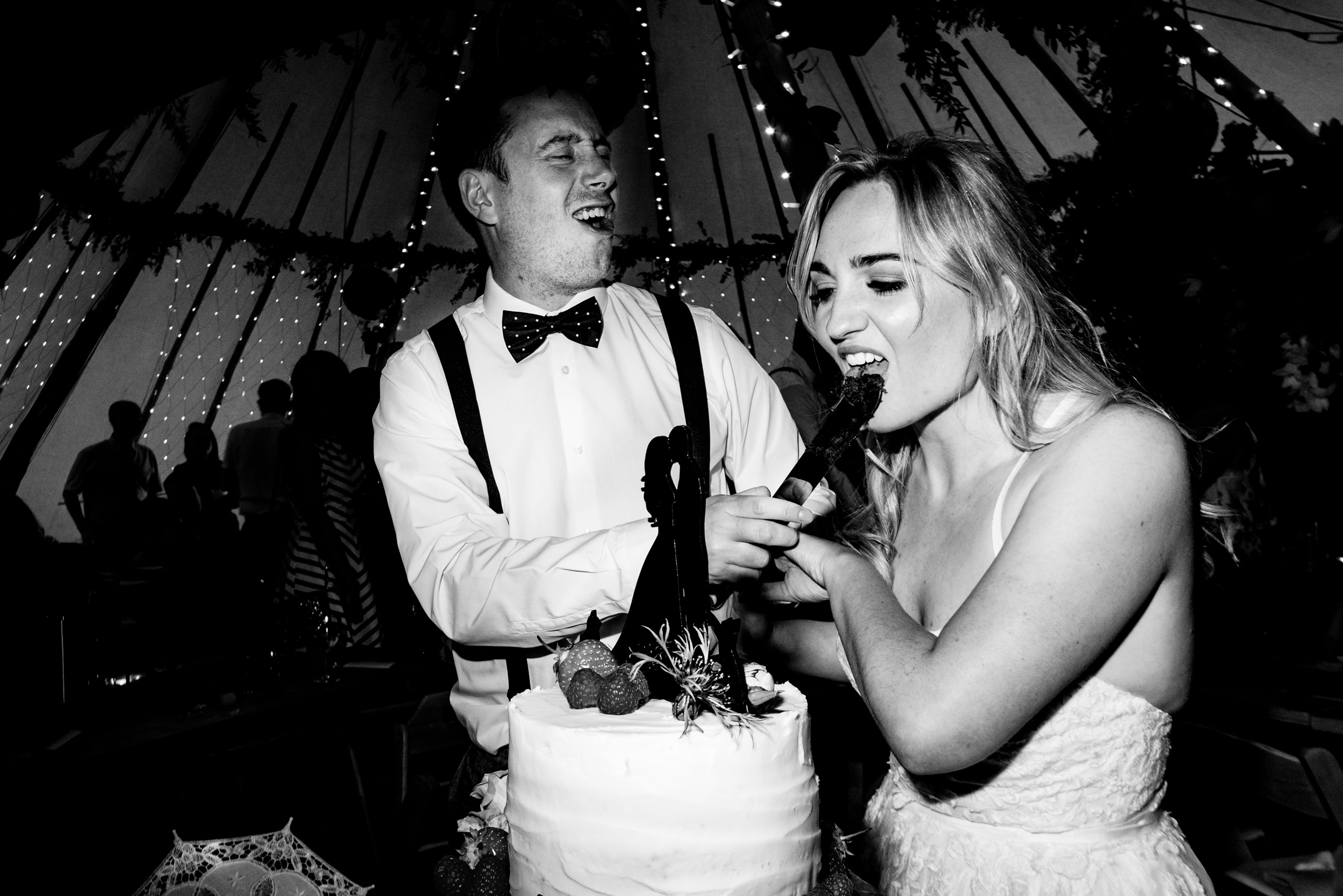 bride licks the knife after cutting the cake. wildwood and eden wedding photography by emma and rich.