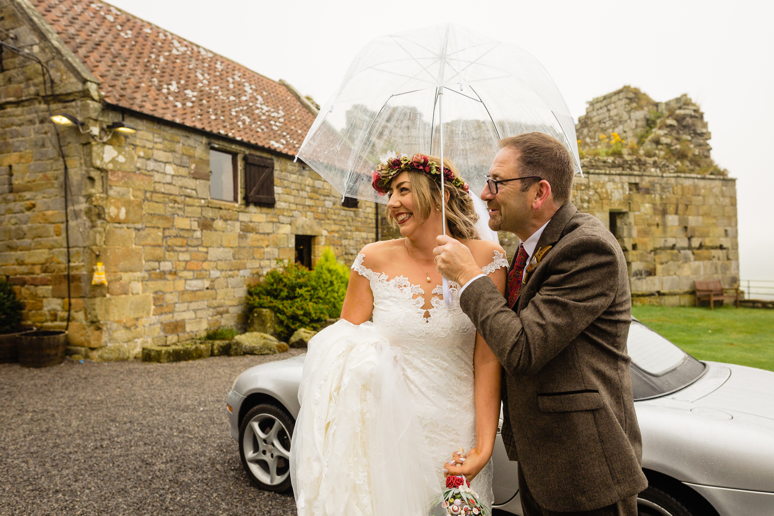 bride and father under umbrella. esk valley wedding photography by emma and rich.