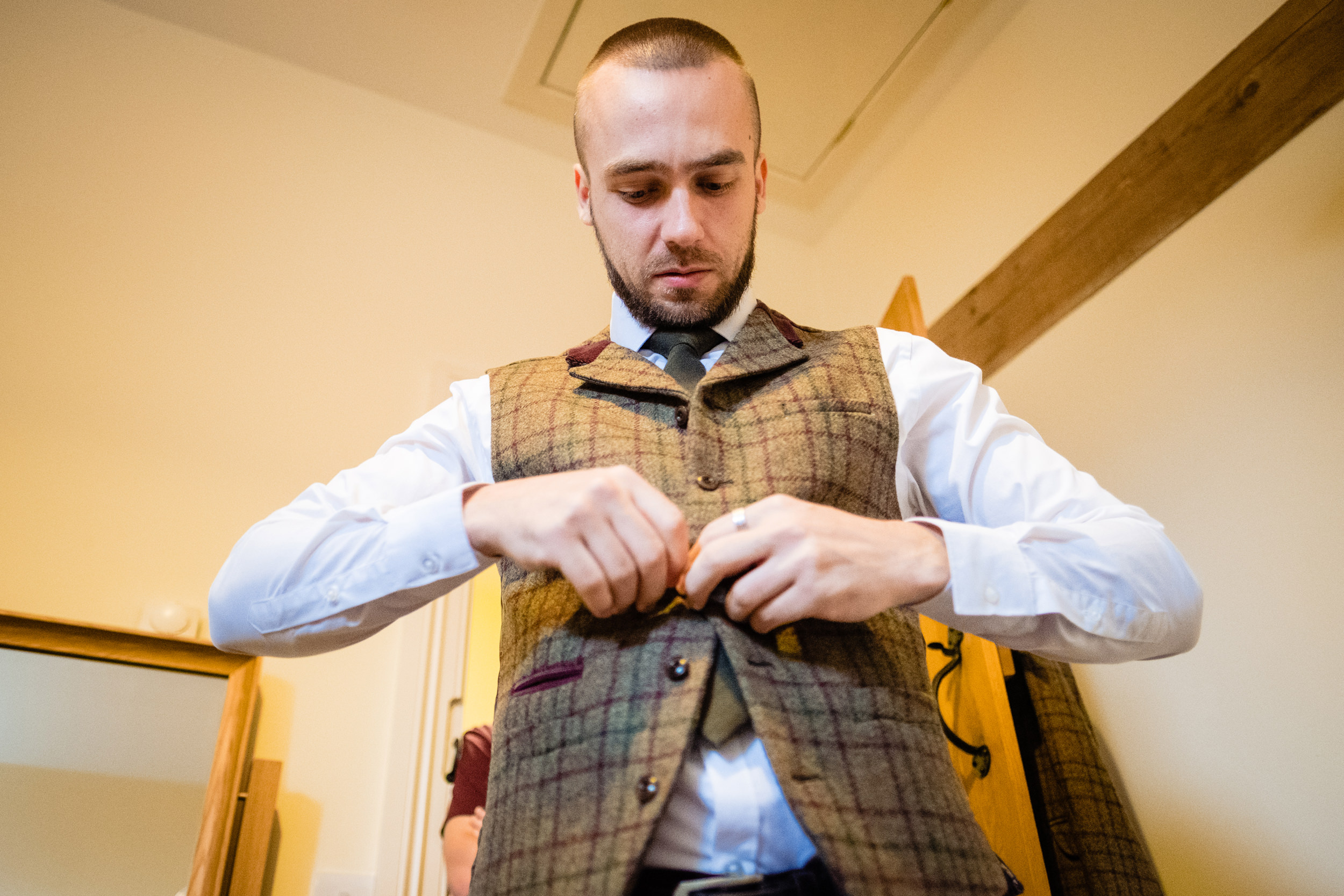 groom putting on his waistcoat. esk valley wedding photography by emma and rich.
