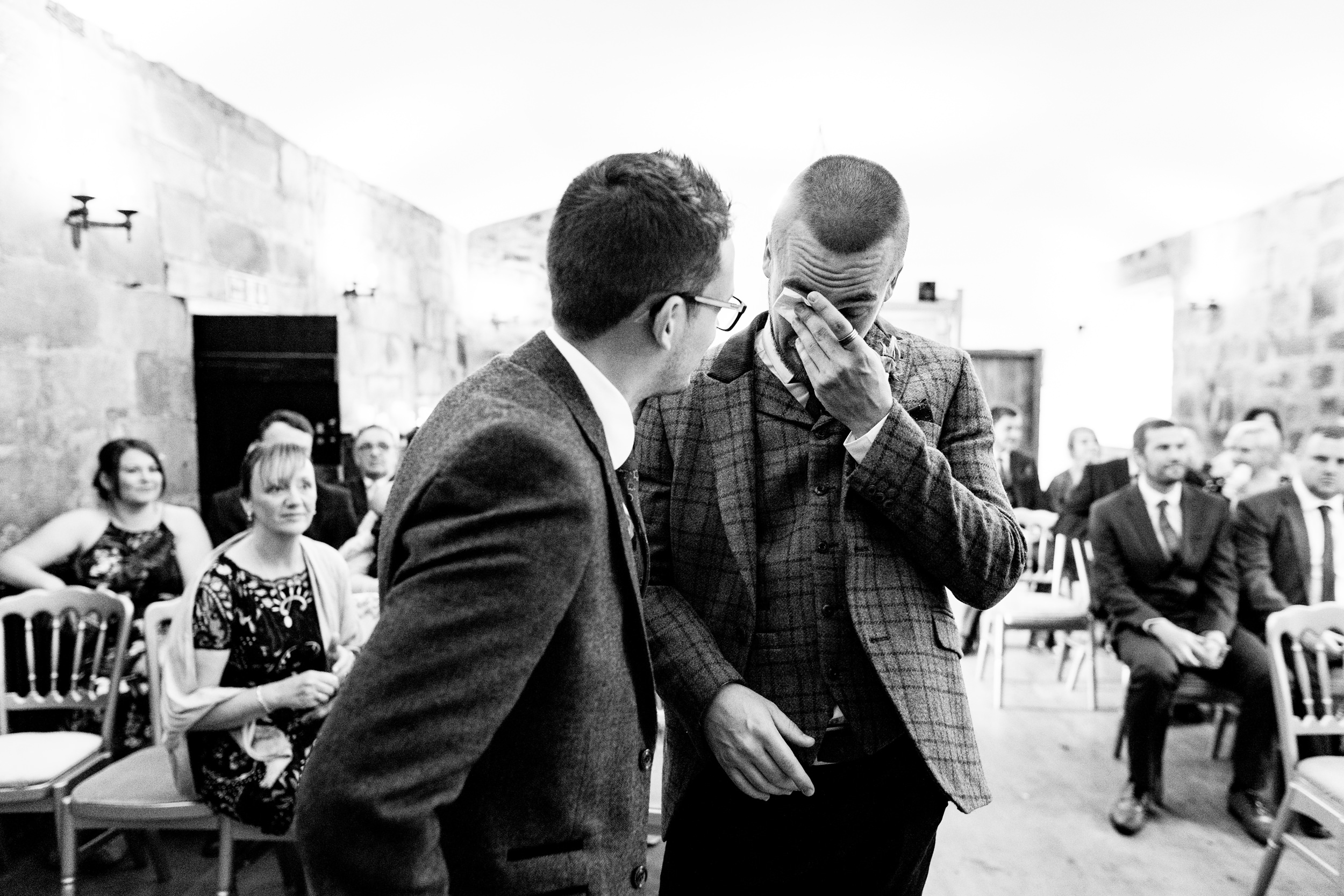 groom wipes tears whilst waiting for bride. esk valley wedding photography by emma and rich.