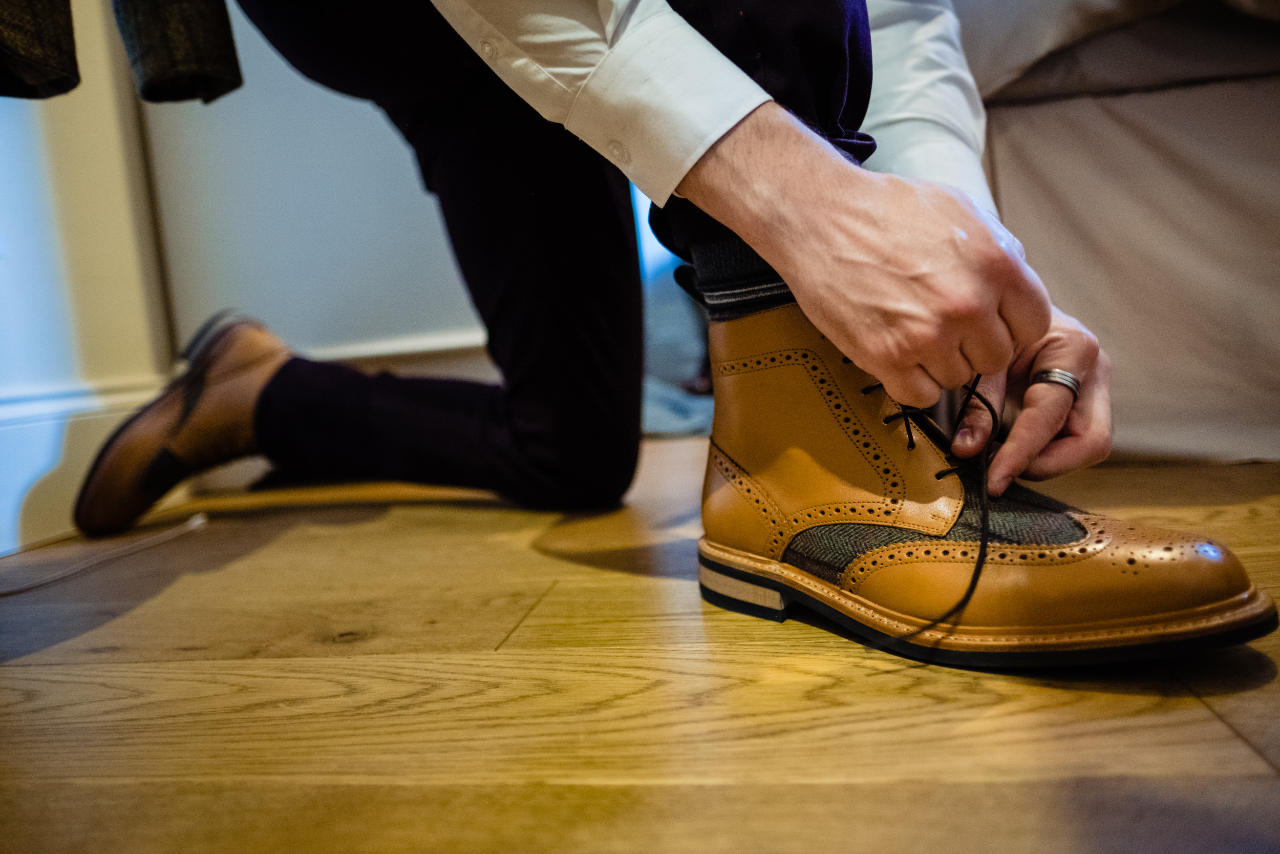 groom putting on shoes. esk valley wedding photography by emma and rich.