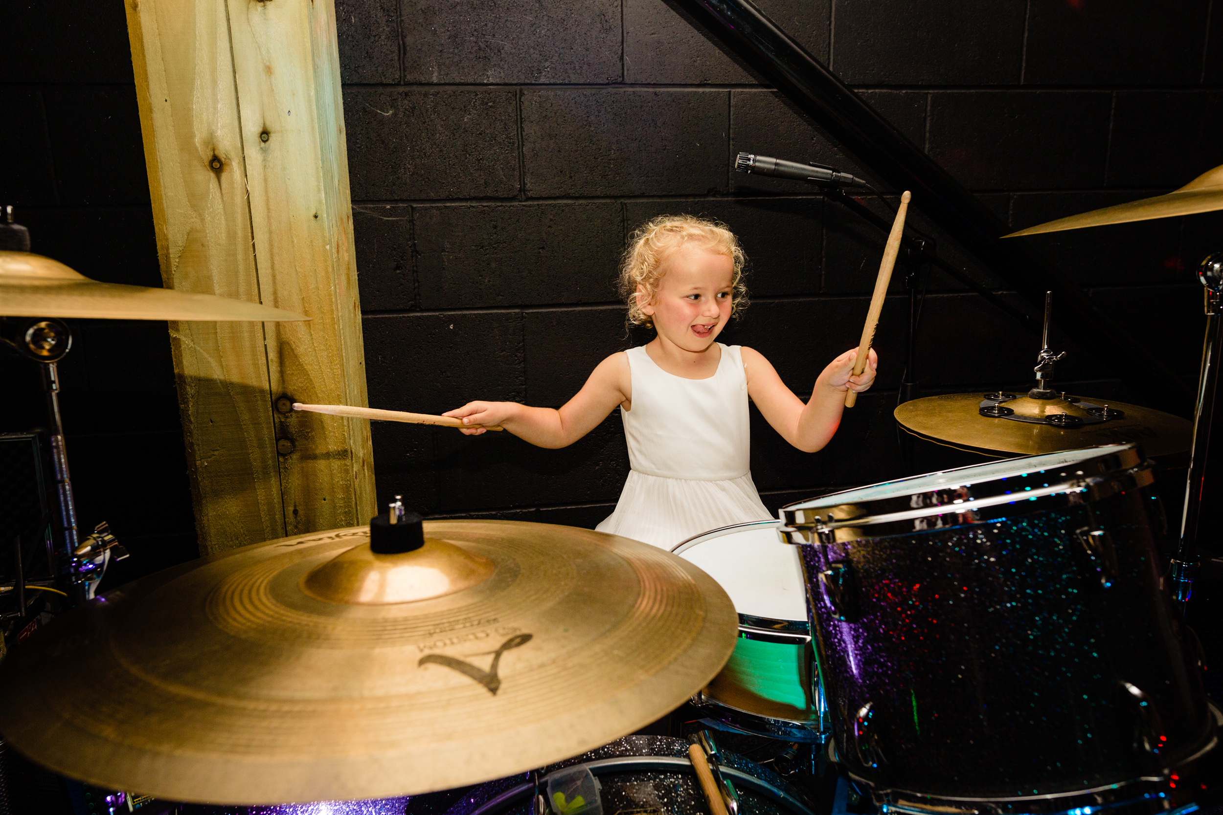 flower girl playing the drums. esk valley wedding photography by emma and rich.