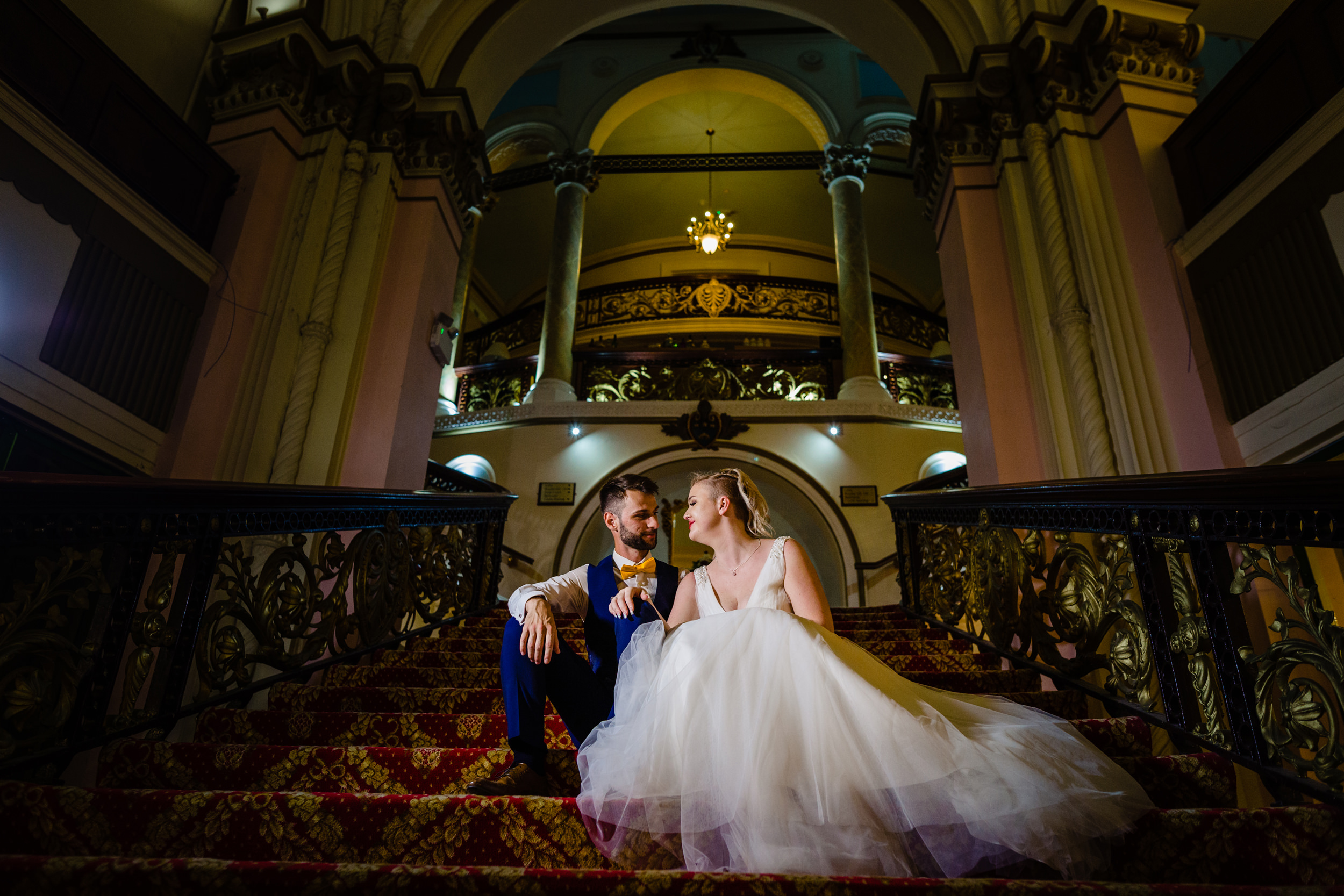 bride and groom sat on staircase. grand hotel scarborough wedding photography by emma and rich.
