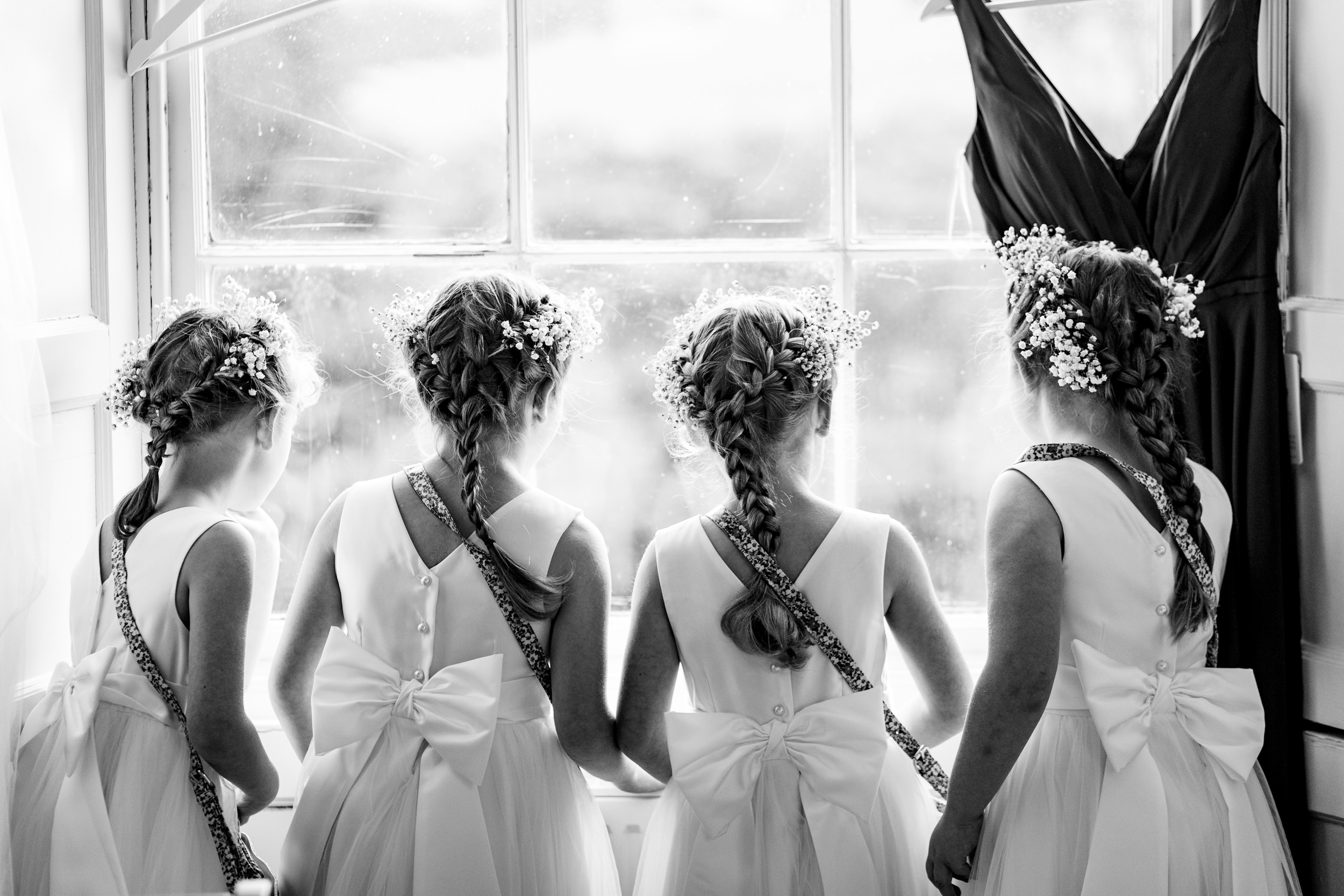 four flower girls looking out of a window. scotland wedding photography by emma and rich.