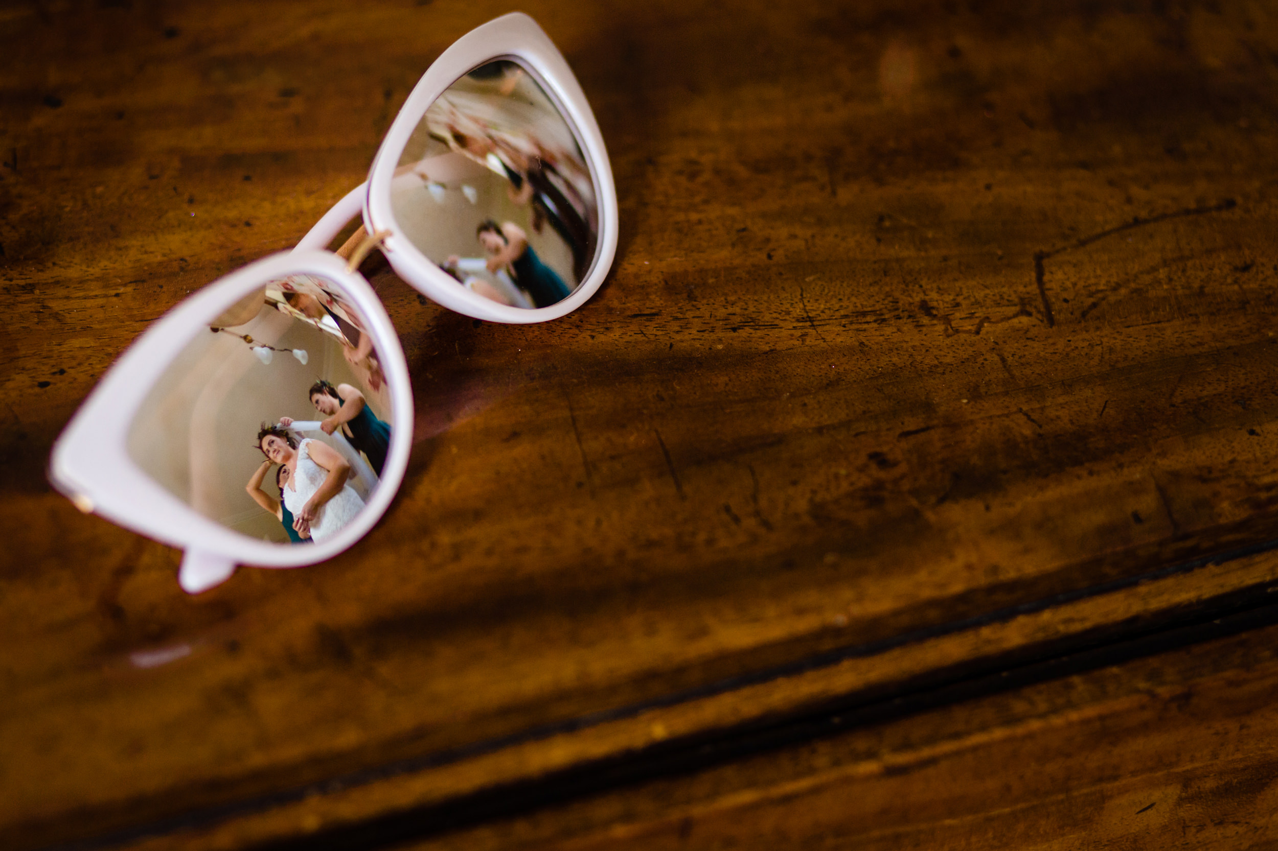 a reflection of a bride having her veil fitted in a pair of sun glasses. scotland wedding photography by emma and rich.