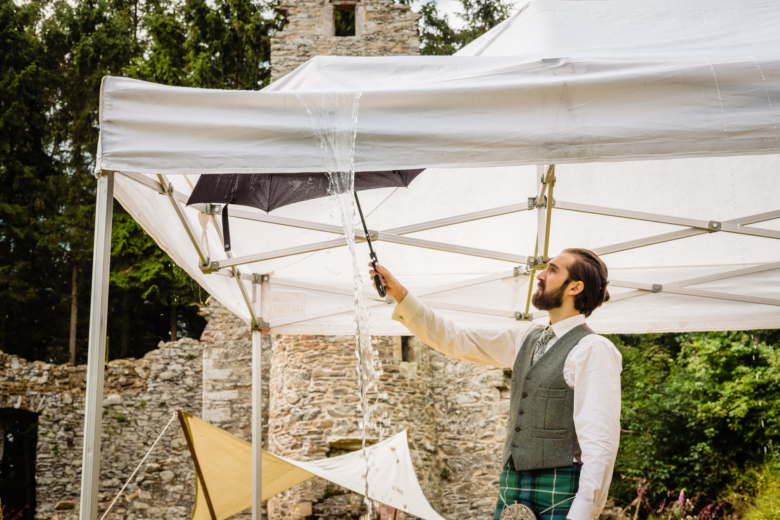 groomsman using an umbrella to clear a marquee roof of water. scotland wedding photography by emma and rich.
