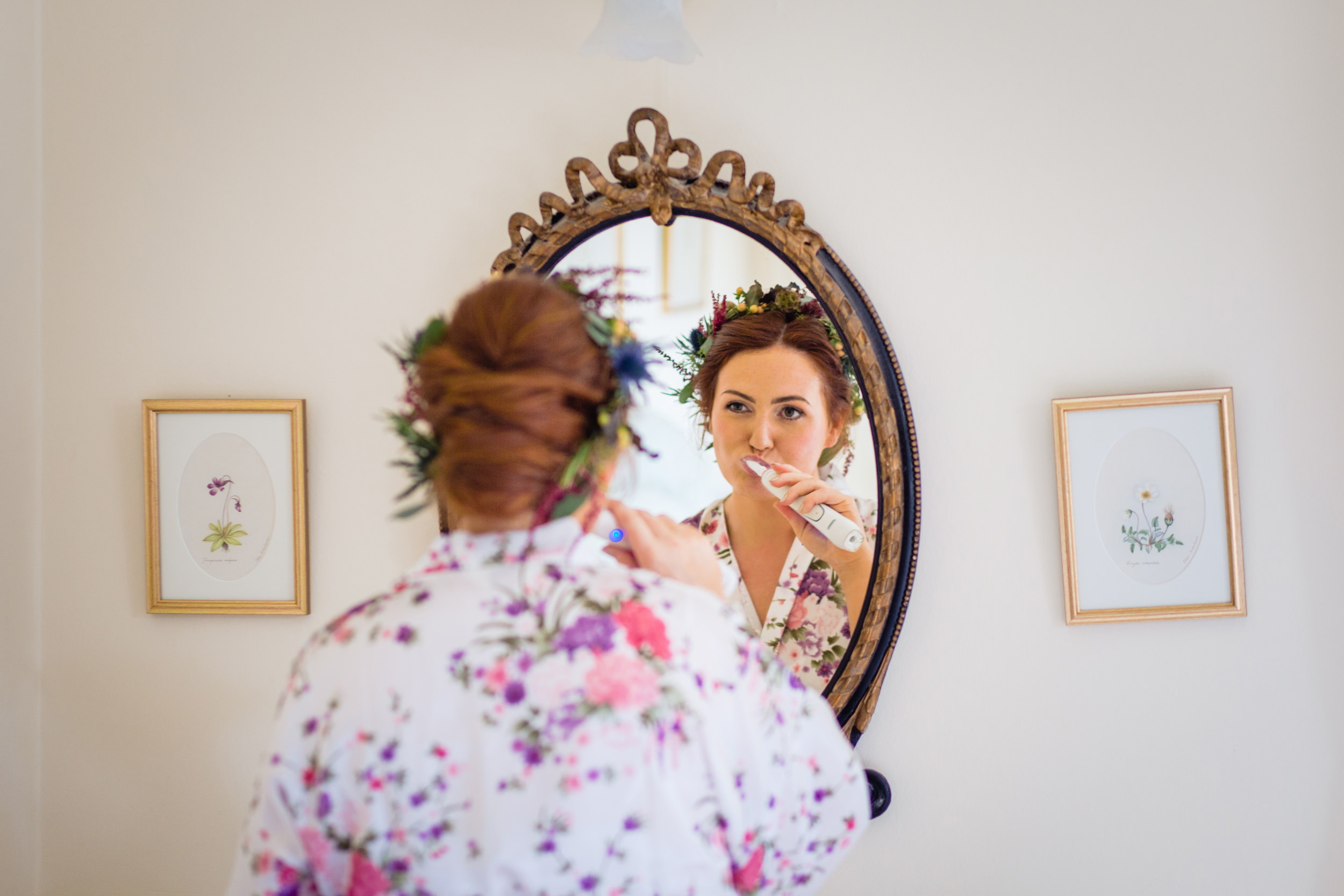 bride brushing her teeth in the mirror. scotland wedding photography by emma and rich.