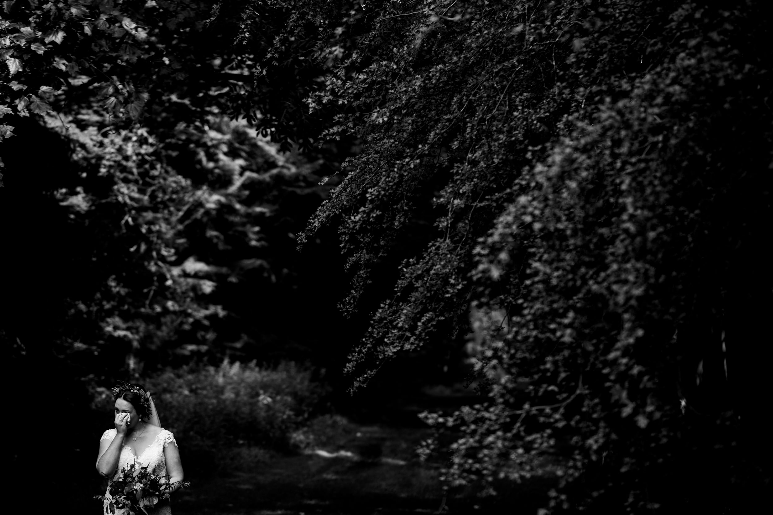 bride wipes tears from eye in woodland clearing. scotland wedding photography by emma and rich.