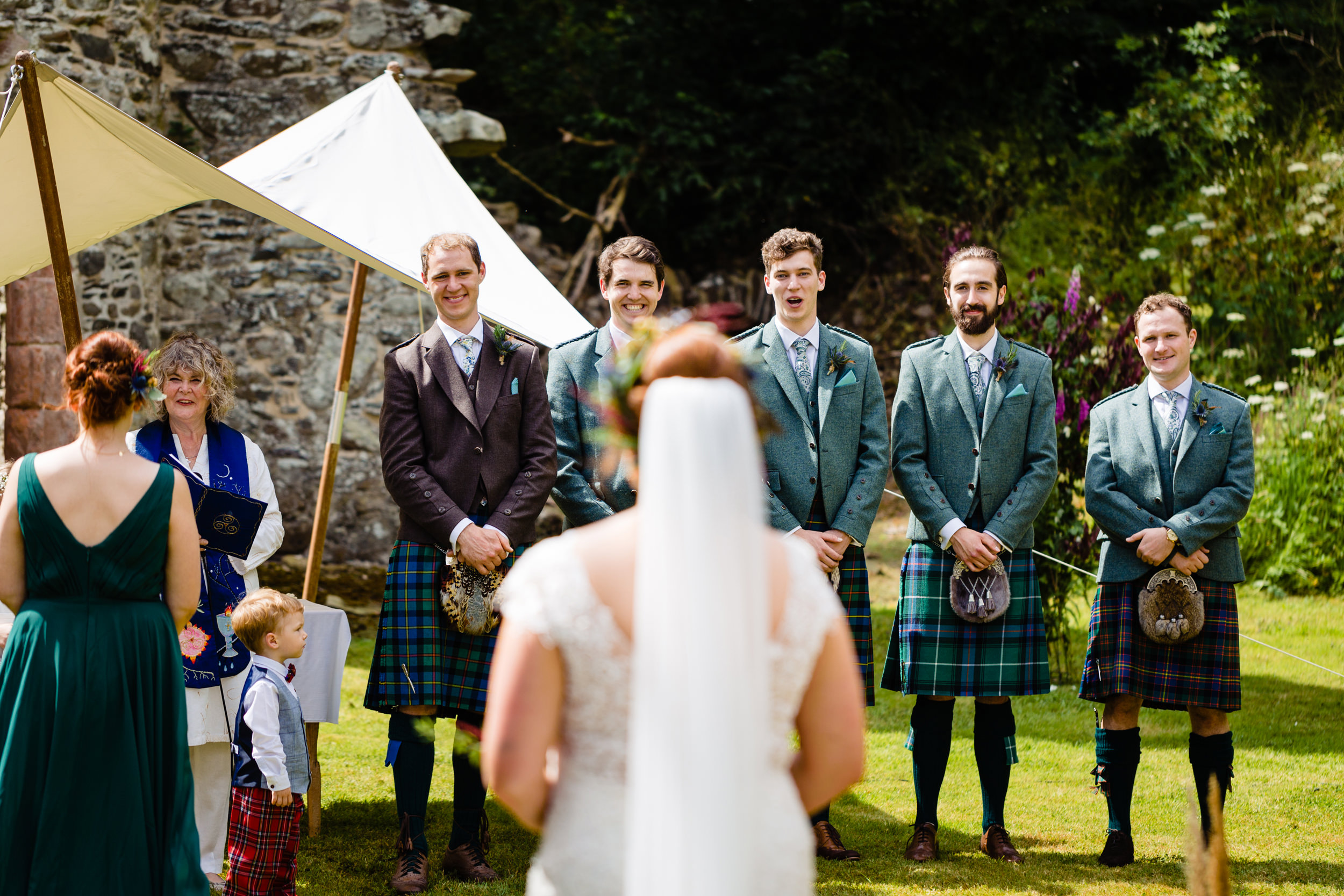 groom smiling at bride walking down the aisle. scotland wedding photography by emma and rich.