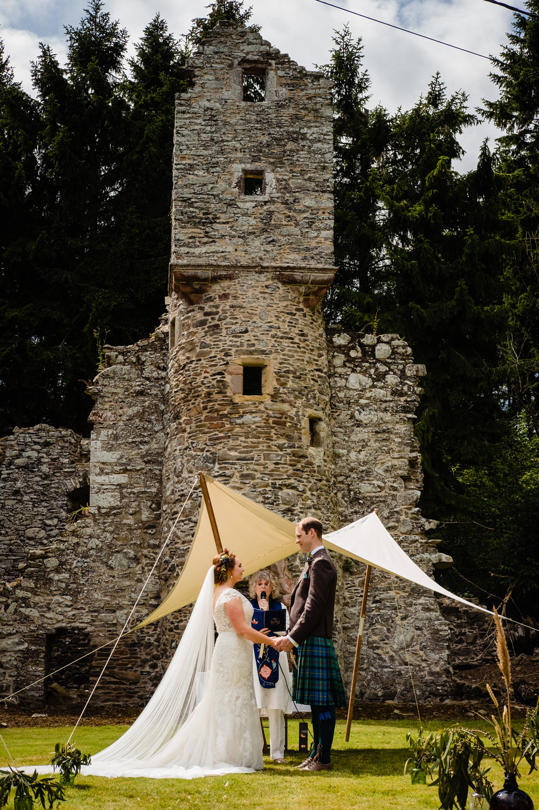 wedding ceremony in front of castle ruins. scotland wedding photography by emma and rich.
