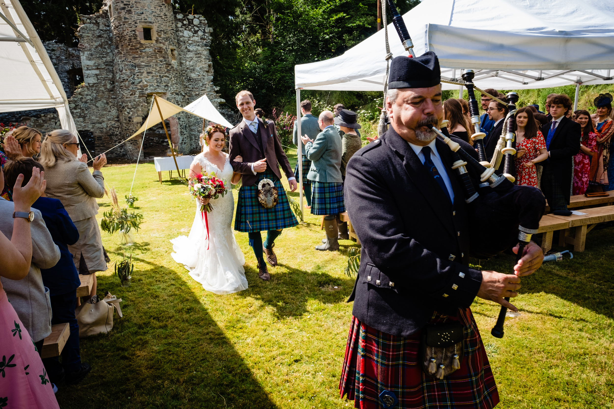 bagpiper leads newly wed couple down the aisle. scotland wedding photography by emma and rich.