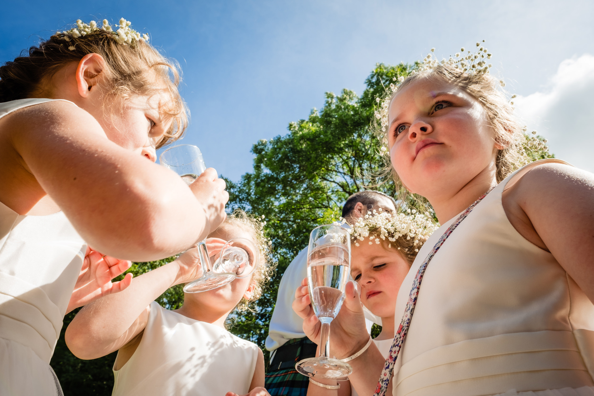 flower girls having a drink. scotland wedding photography by emma and rich.