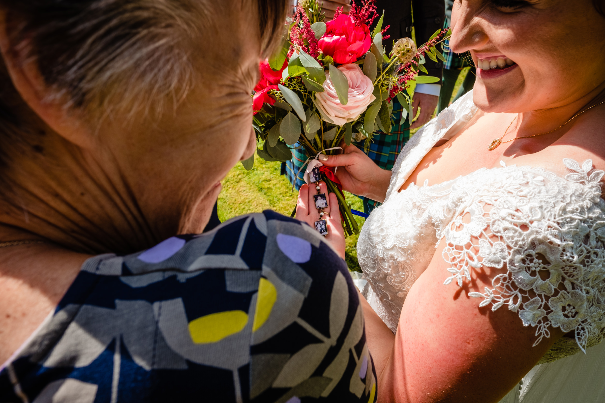bride and guest looking at bouquet. scotland wedding photography by emma and rich.