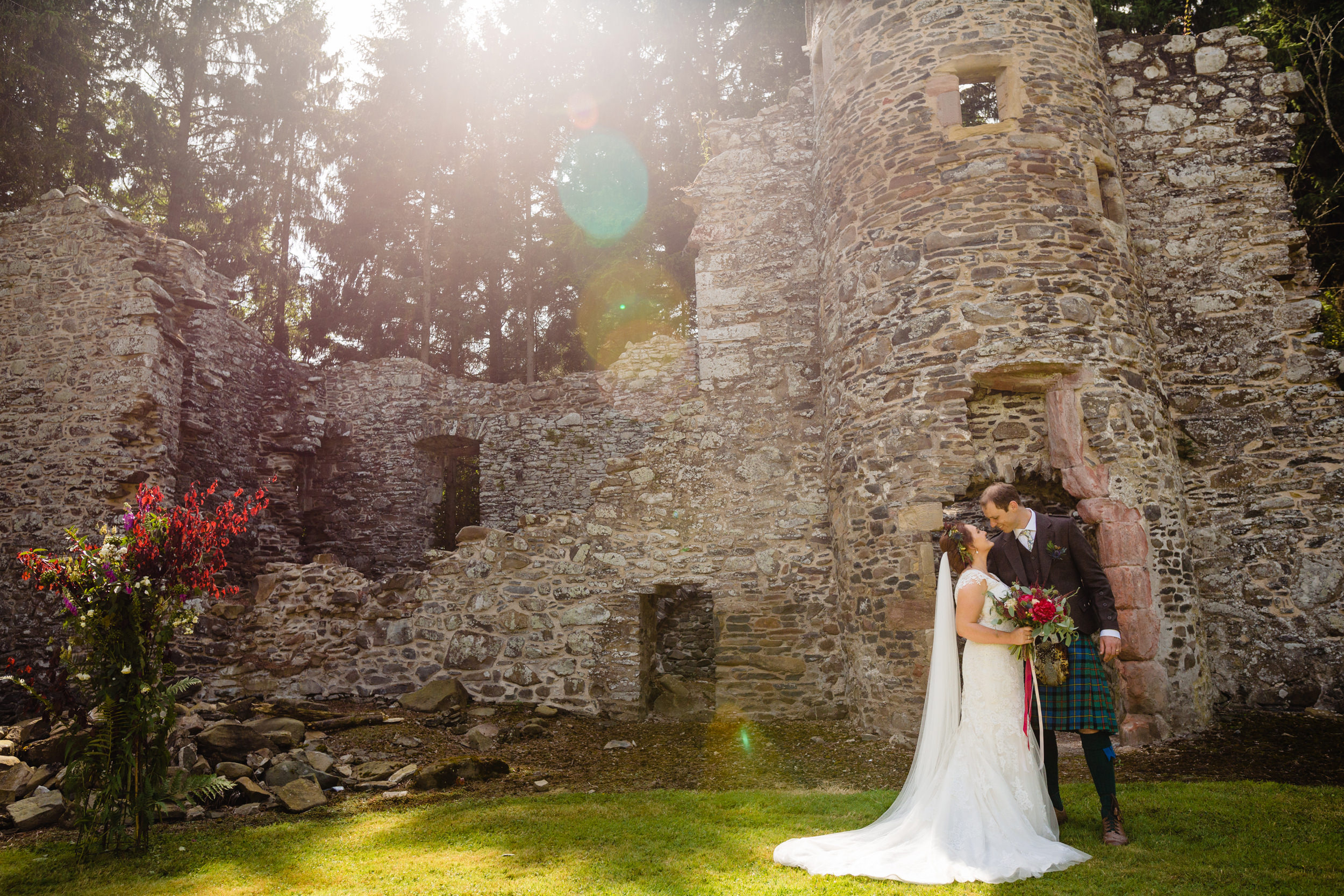 bride and groom in front of castle ruins. scotland wedding photography by emma and rich.