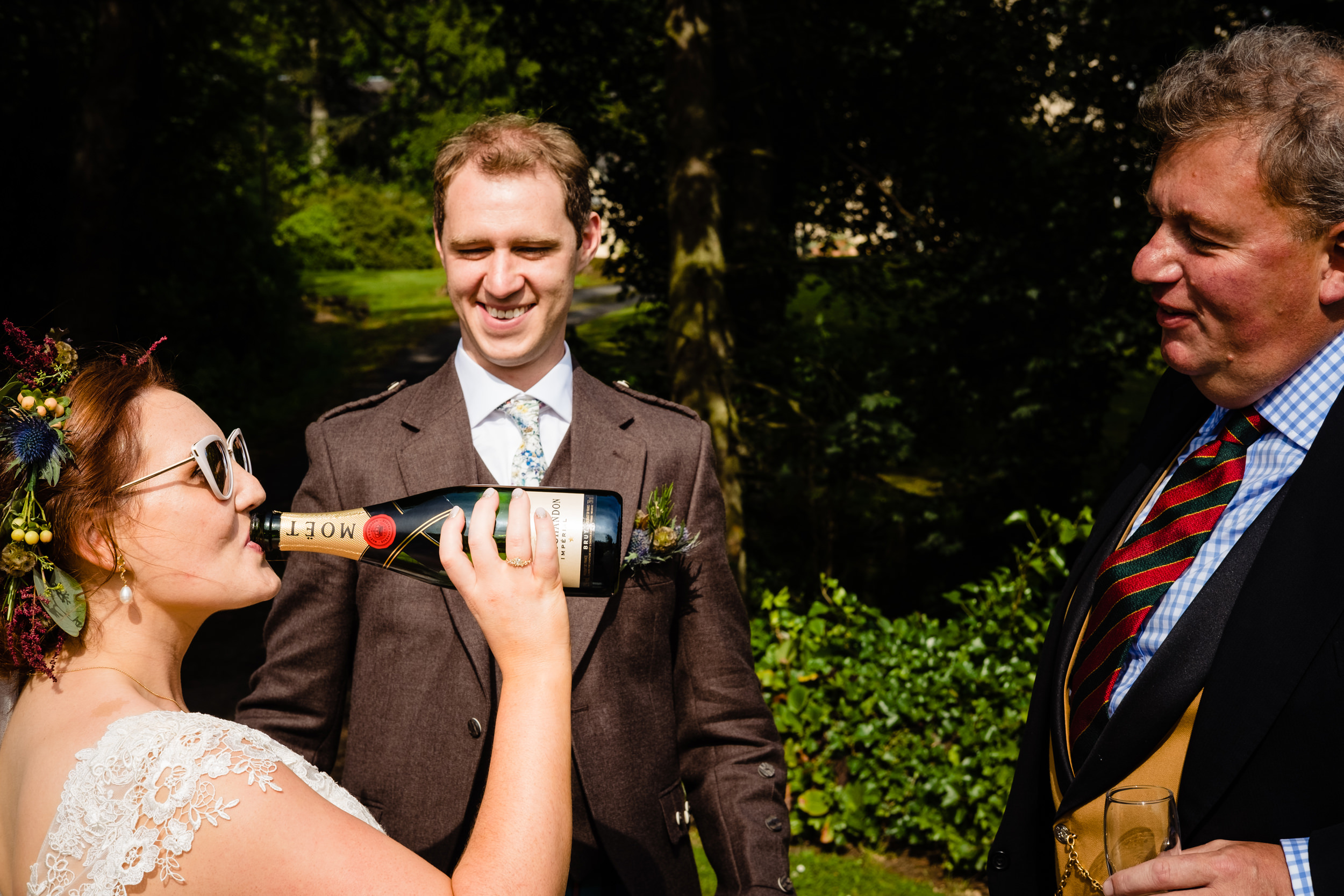 bride drinking champagne from the bottle. scotland wedding photography by emma and rich.