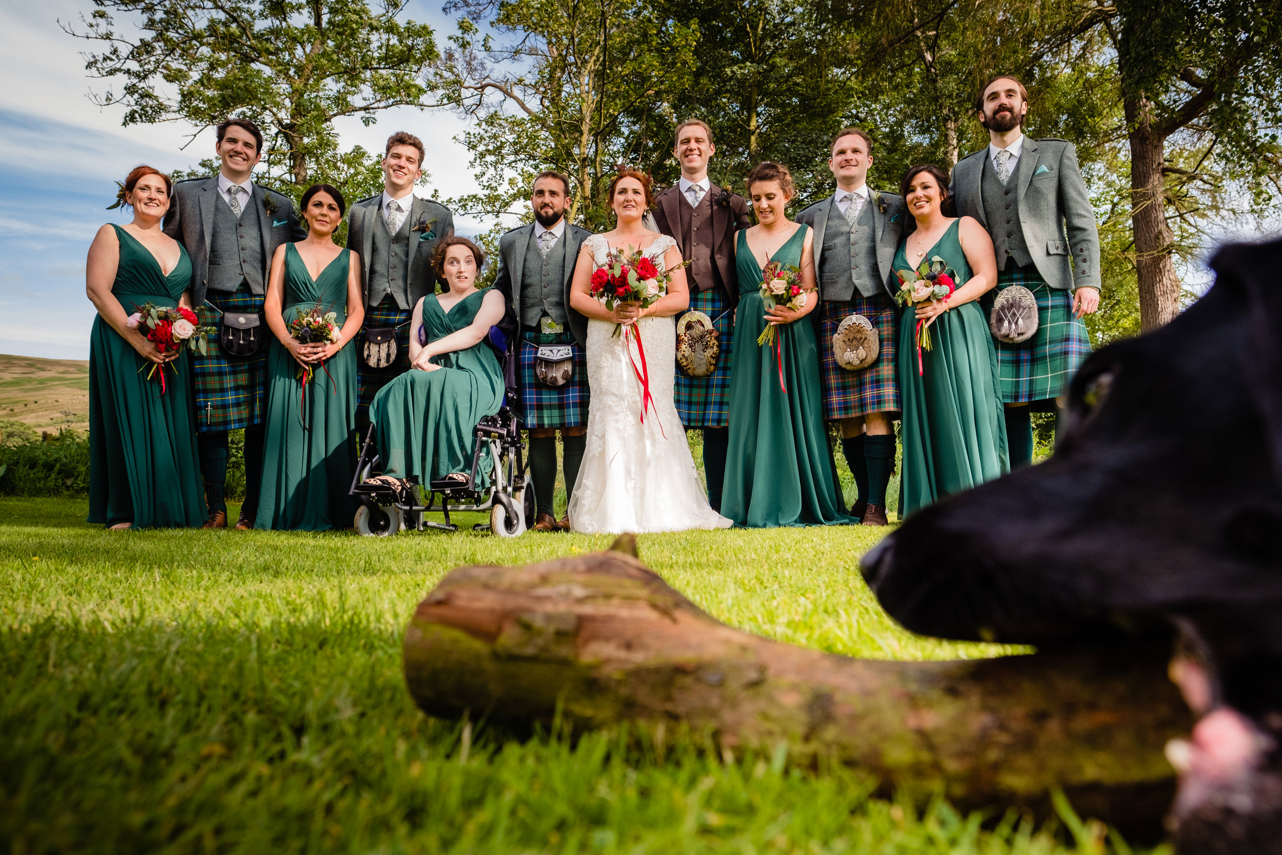 dog in front of group shot. scotland wedding photography by emma and rich.